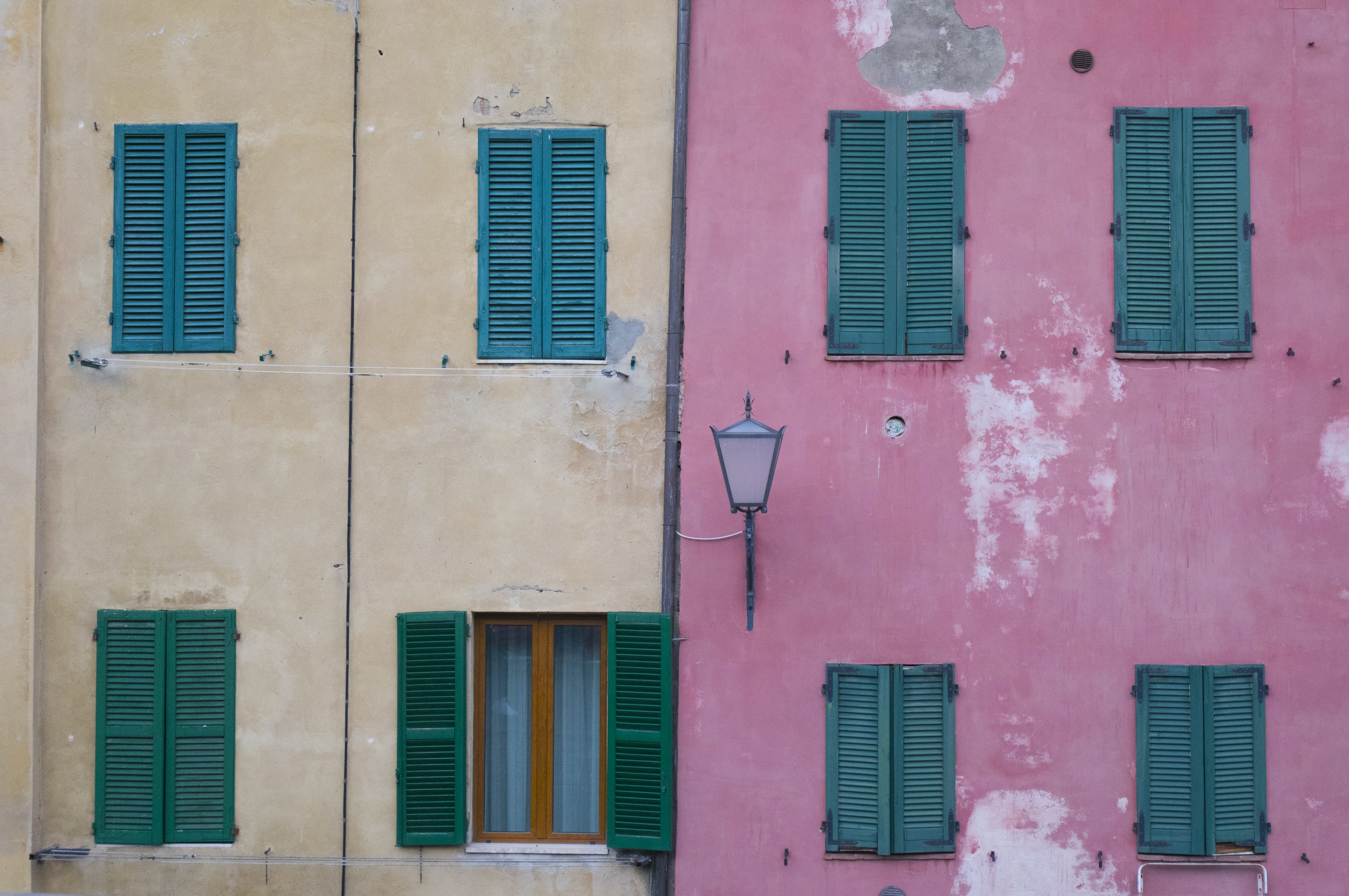 An old building with beige and pink walls with green window shutters in Siena.