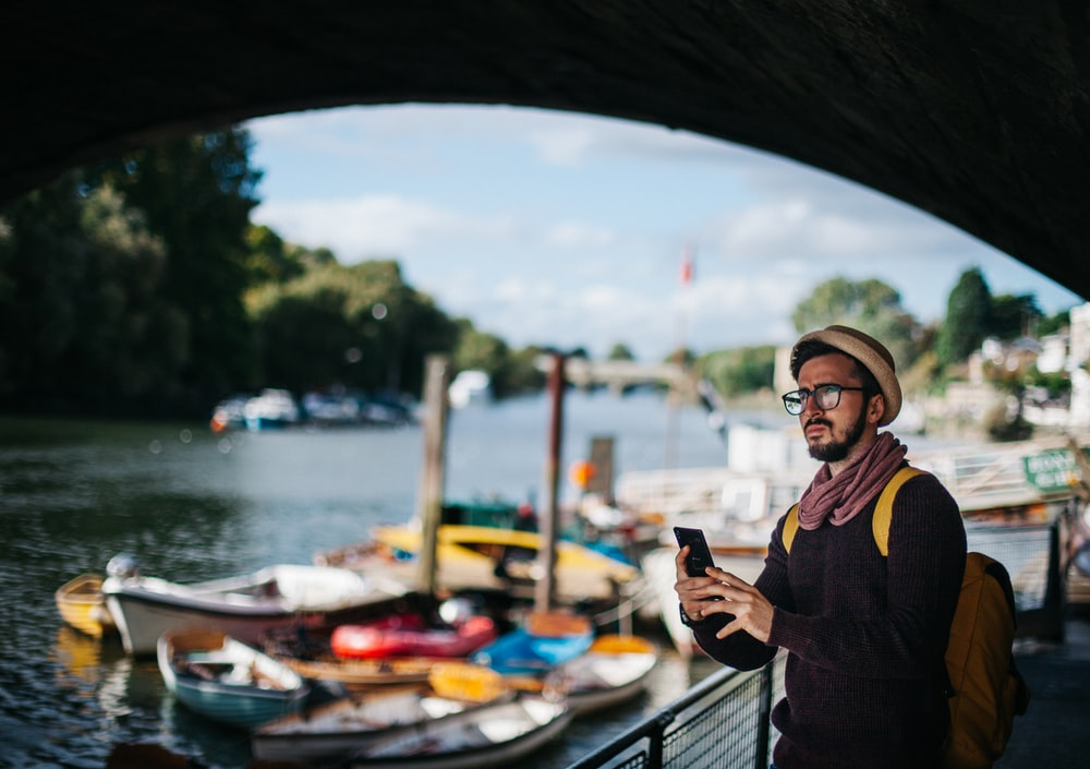 man holding phone under bridge