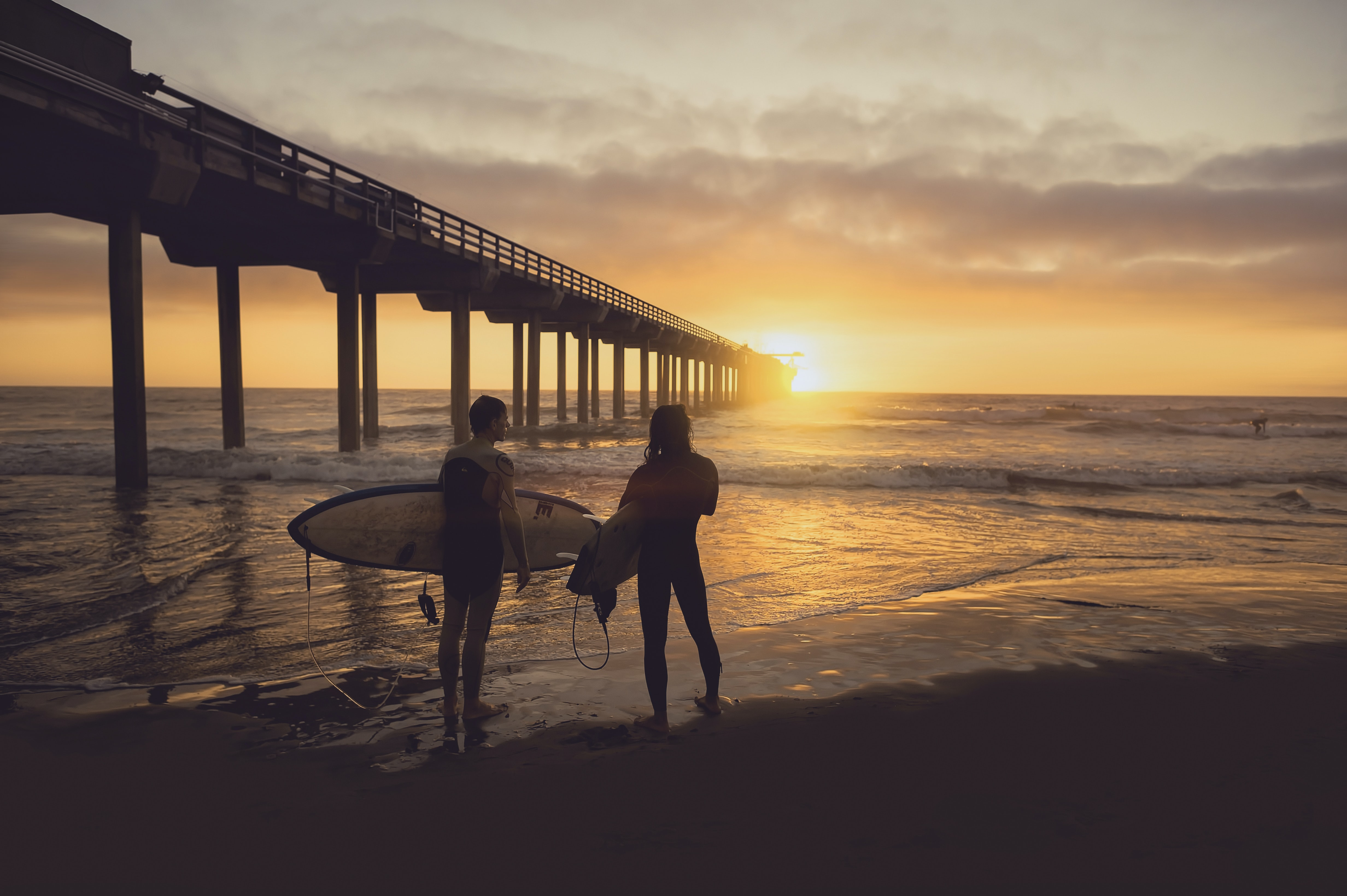 Two surfers standing on the sand beach by the wooden pier pillars at sunset