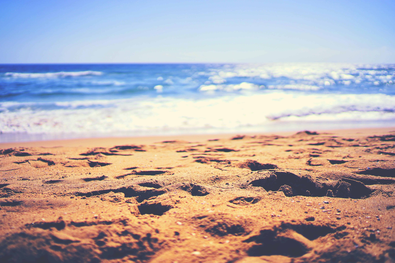 Sand beach by the sun lit blue ocean in Santa Monica