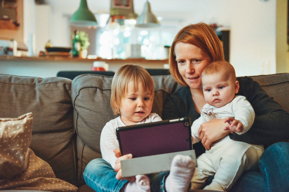 two babies and woman sitting on sofa while holding baby and watching on tablet