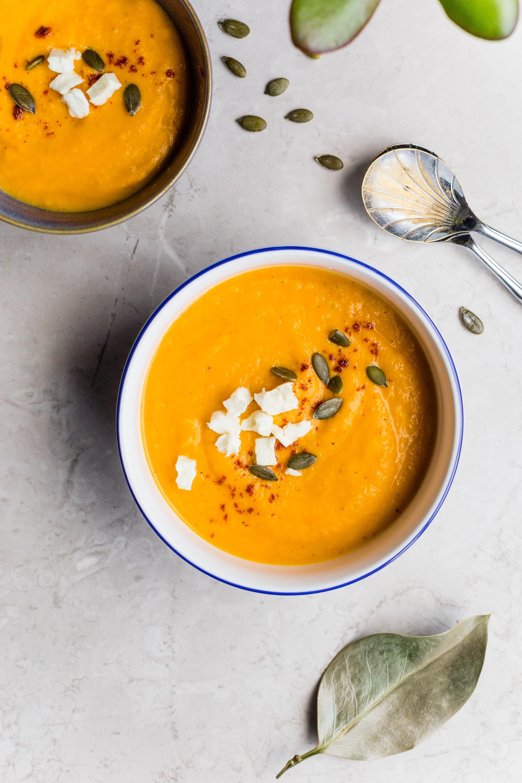フェタチーズとハーブをトッピングしたオレンジのスカッシュスープのボウル