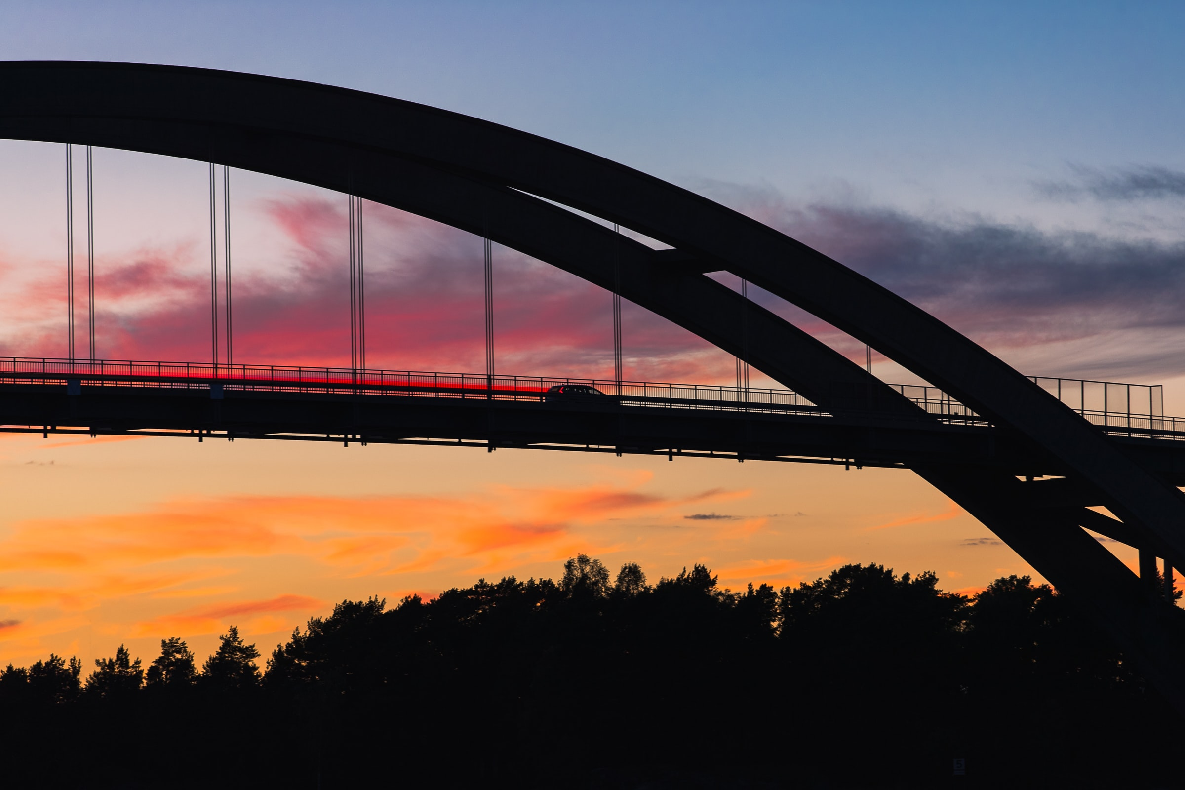 Arched bridge silhouetted against a colorful sunset
