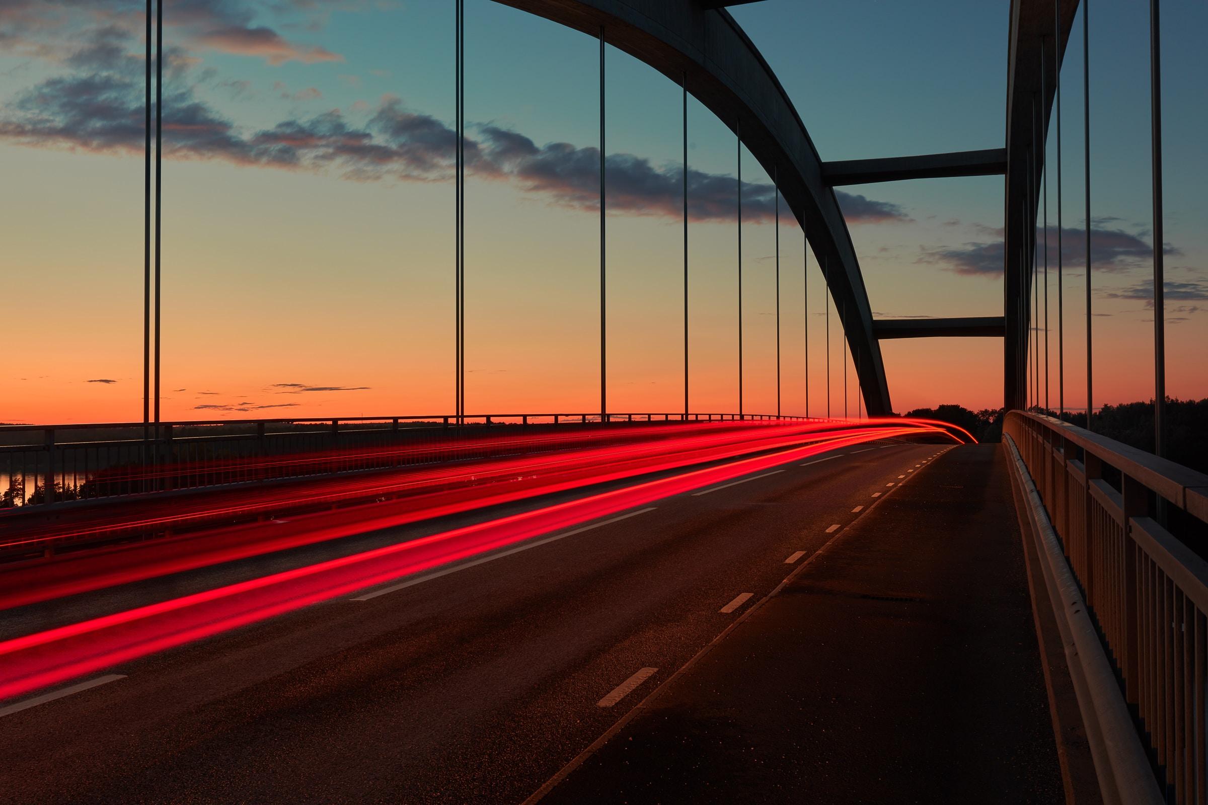 A blurry shot taken at sunrise, featuring a traffic light trail on a bridge in Djuröbron
