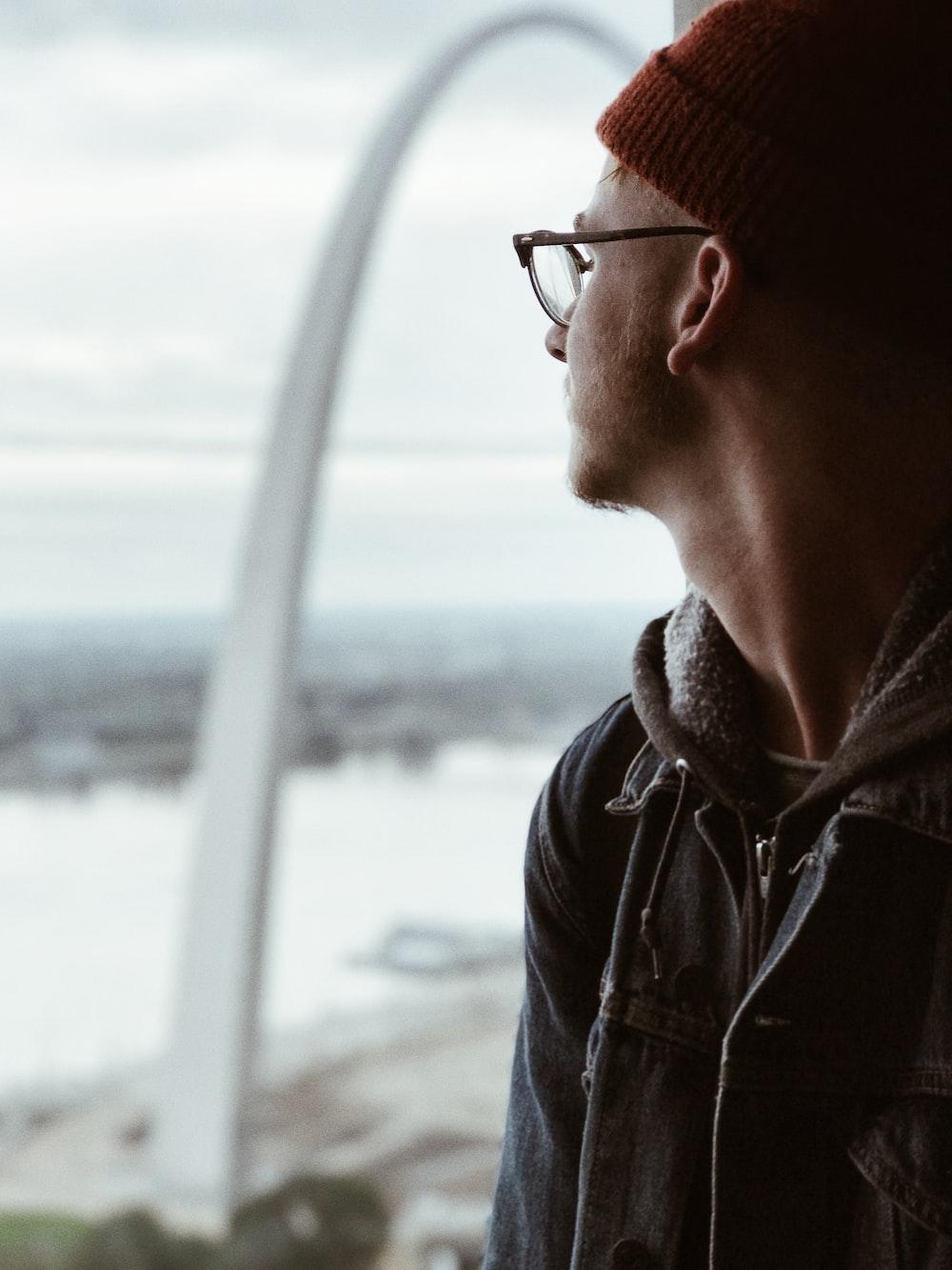 man in denim jacket standing beside window looking outside