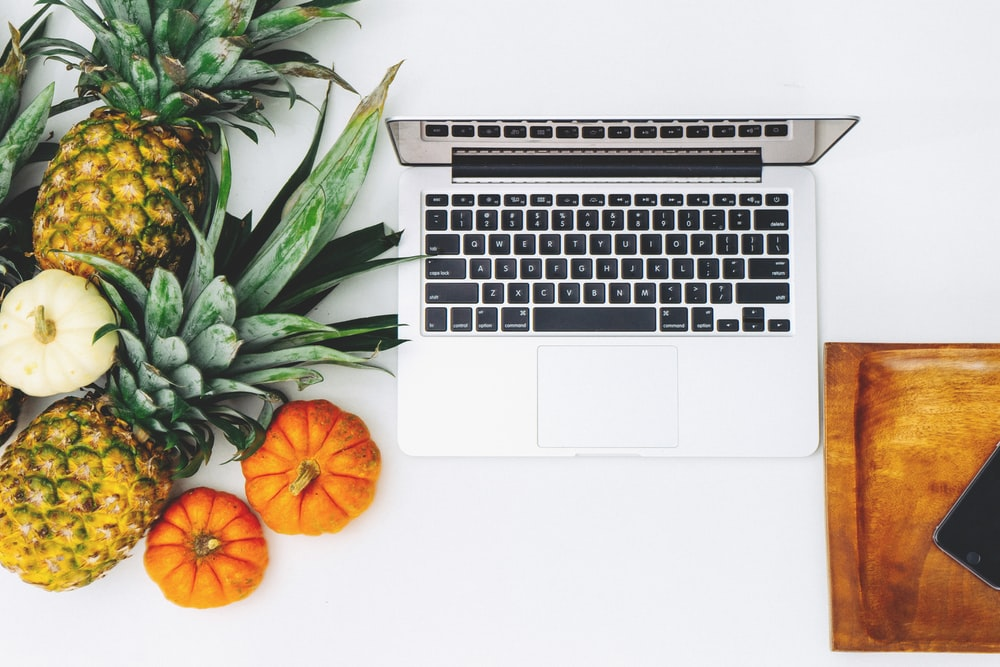 MacBook Pro and assorted fruits flat lay photography