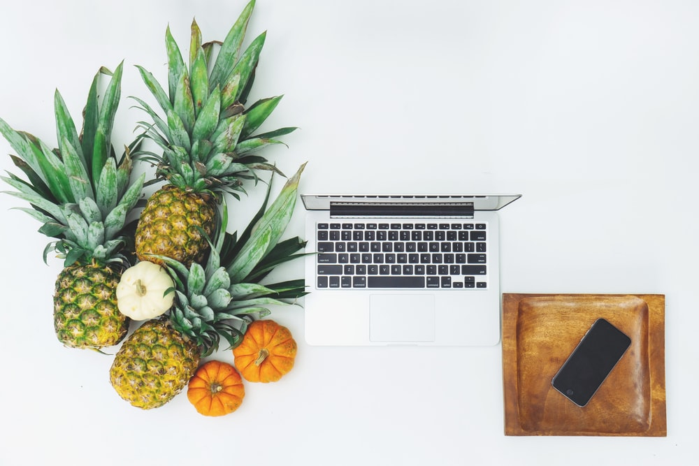 pineapple fruits near MacBook on white surface