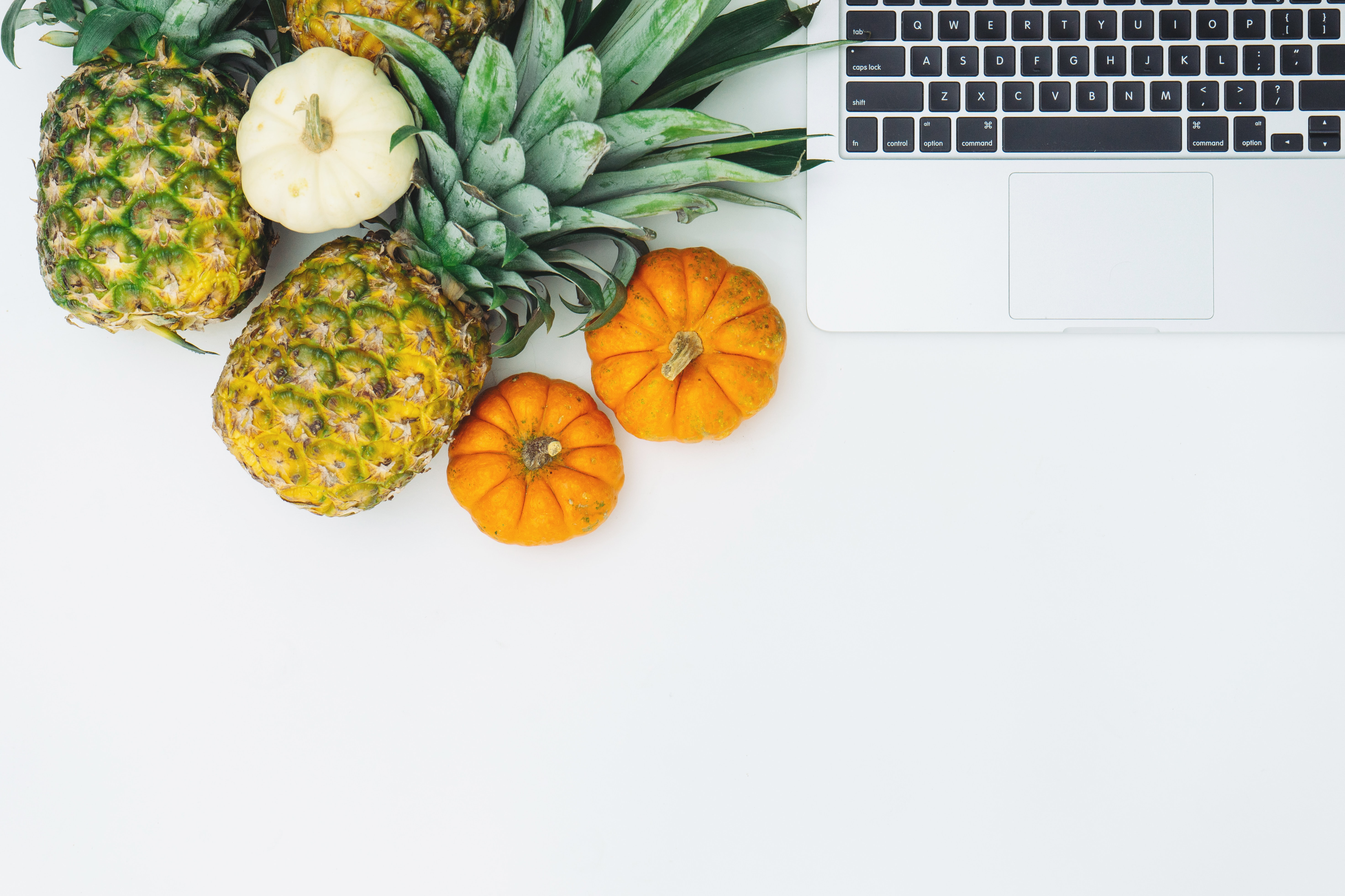 Top view of pineapples and miniature pumpkins and a Macbook.