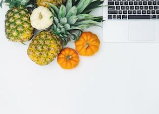 green pineapple fruit near MacBook