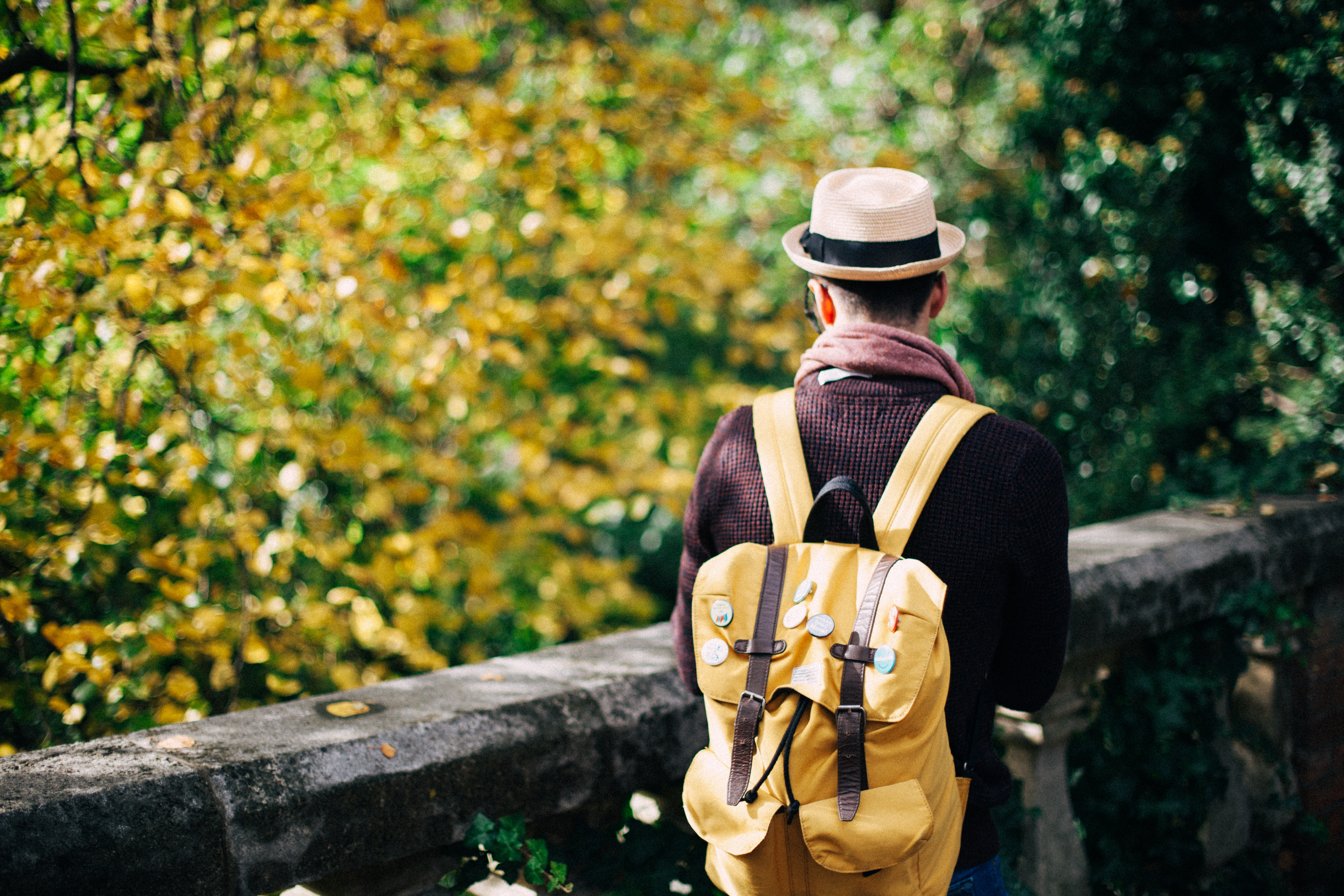 A man wearing a hat and traveling alongside the trees on a walking path in Richmond