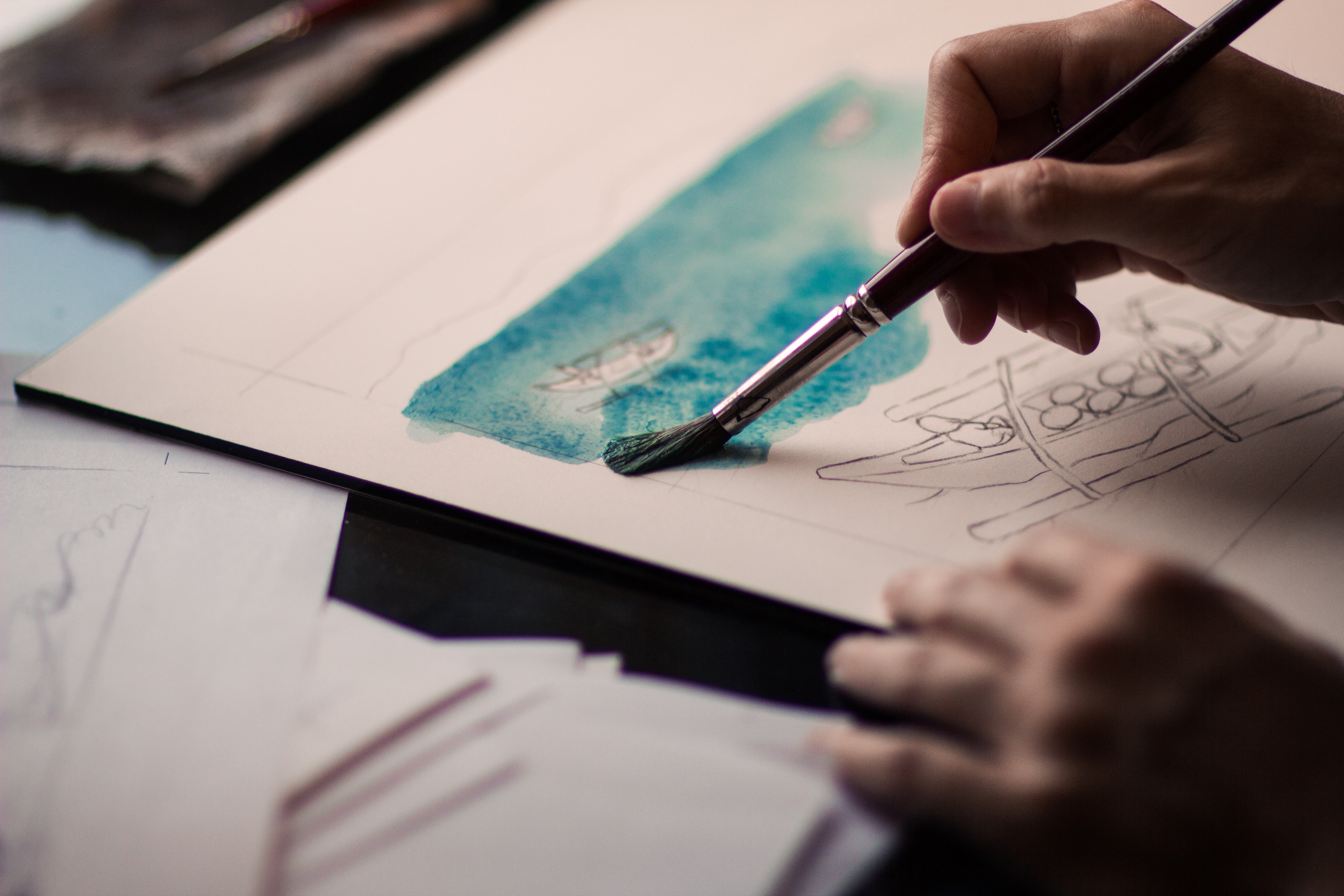 Person painting on white paper with blue watercolor paint
