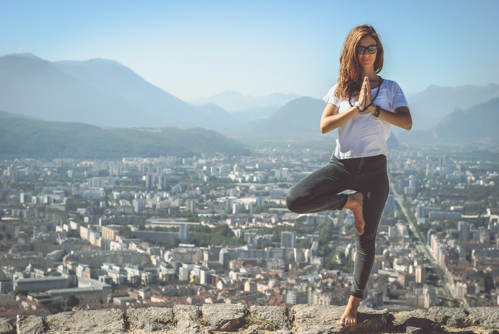 A woman meditating outside, with a view of the city.