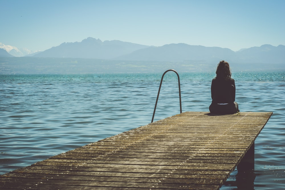 a woman sits on the end of a dock during daytime staring across a lake
