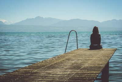 a woman sits on the end of a dock during daytime staring across a lake sadness zoom background