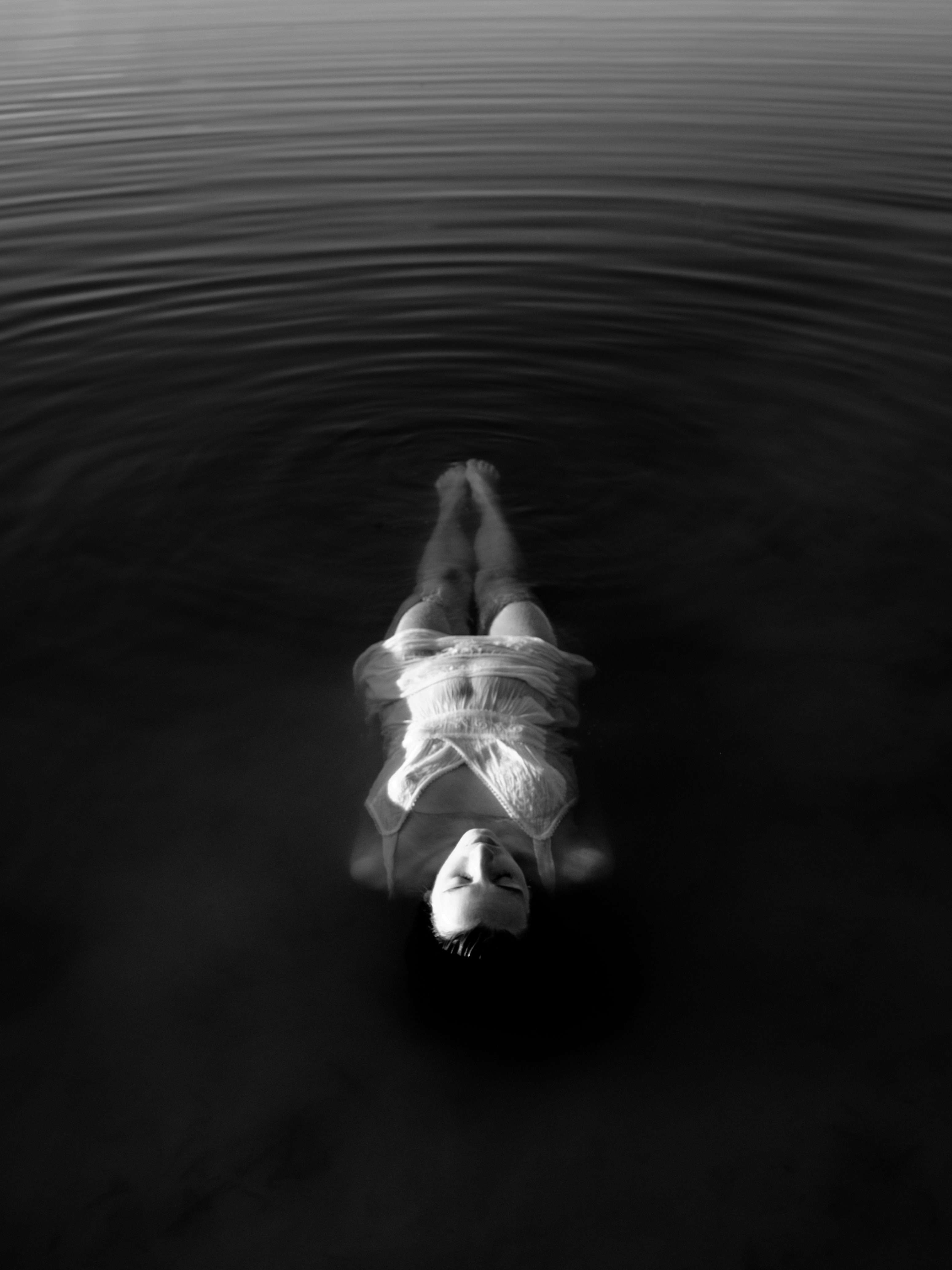 Black and white shot of woman floating in water with ripples in Wassenaar, Zuid-Holland, Nederland
