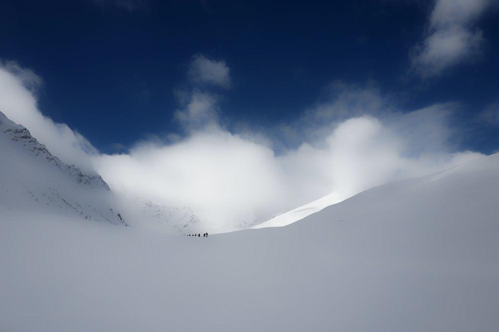 people walking on snow under cloudy sky