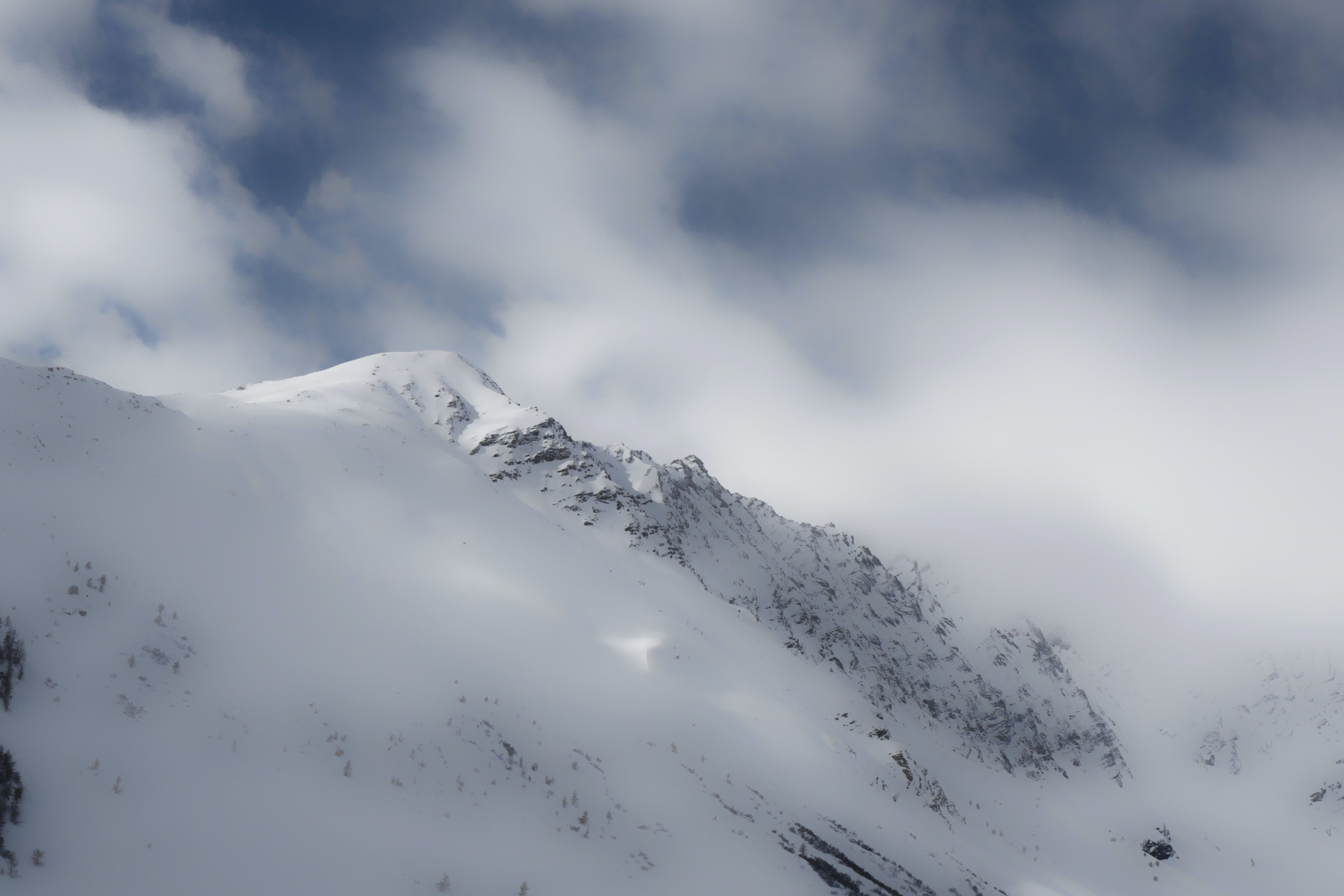 Clouds cover a snowy mountain ridge