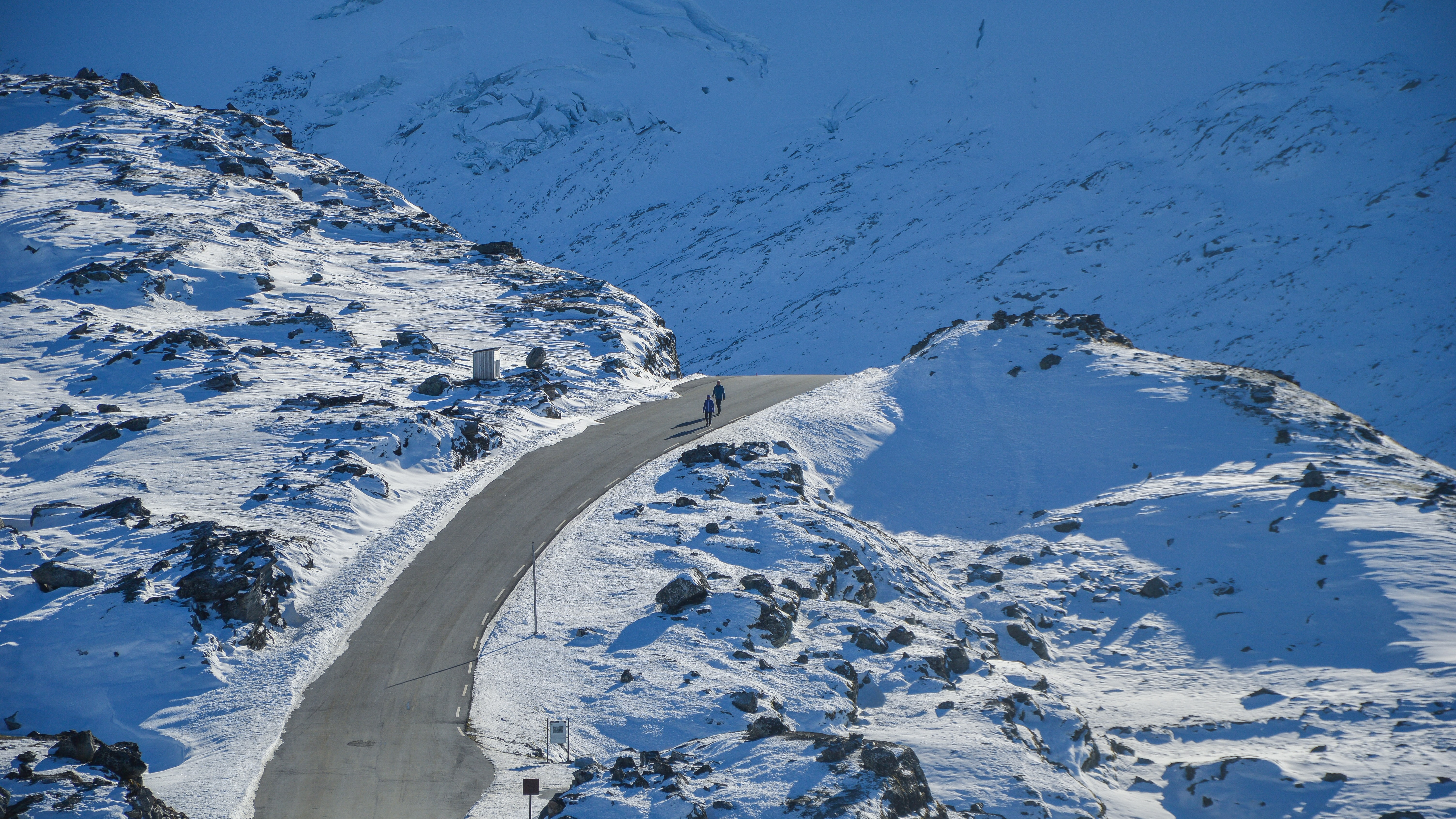 bird's eye photography of two people walking on road between snowfield