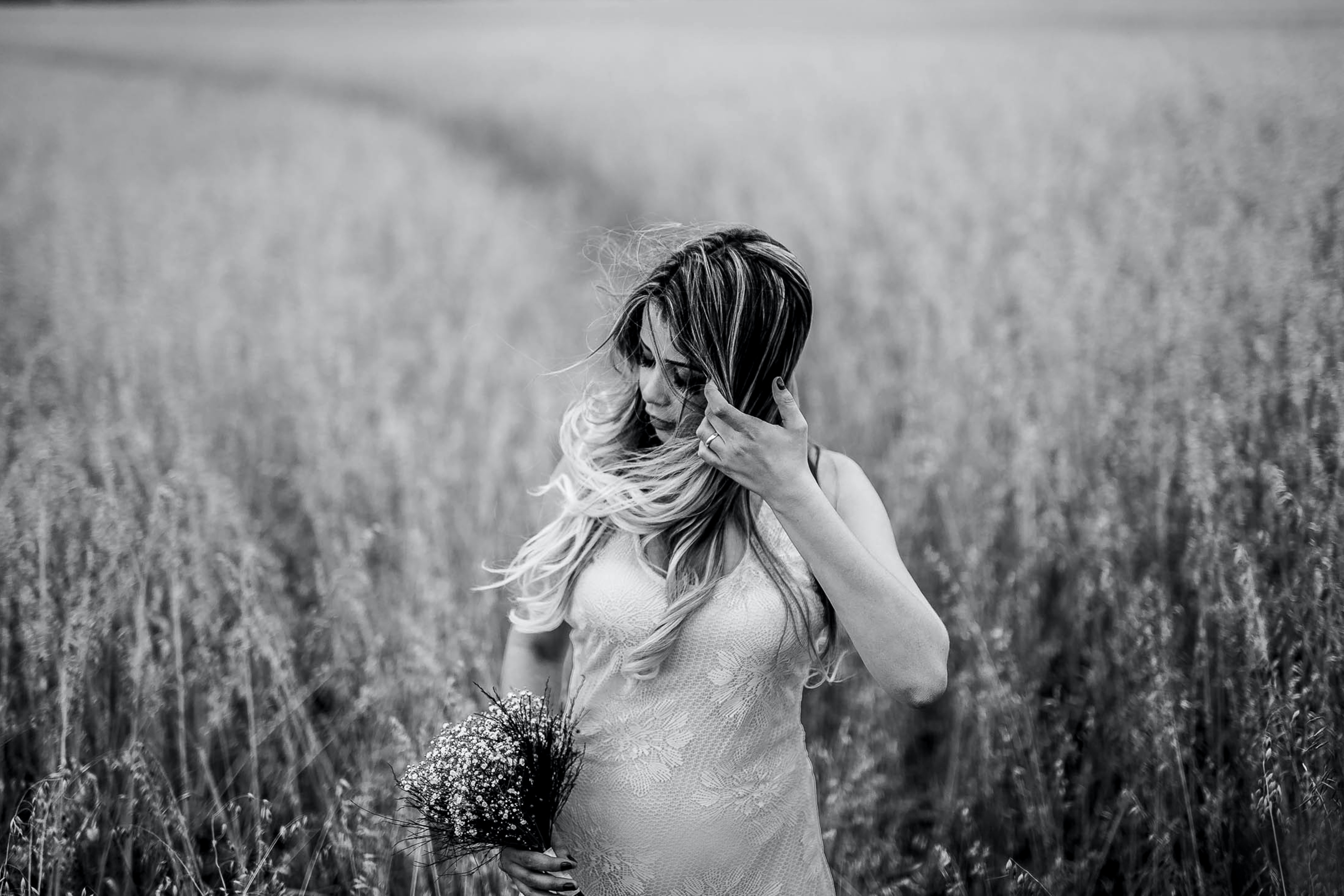 A black-and-white shot of a woman with a floral bouquet brushing back her hair in a field