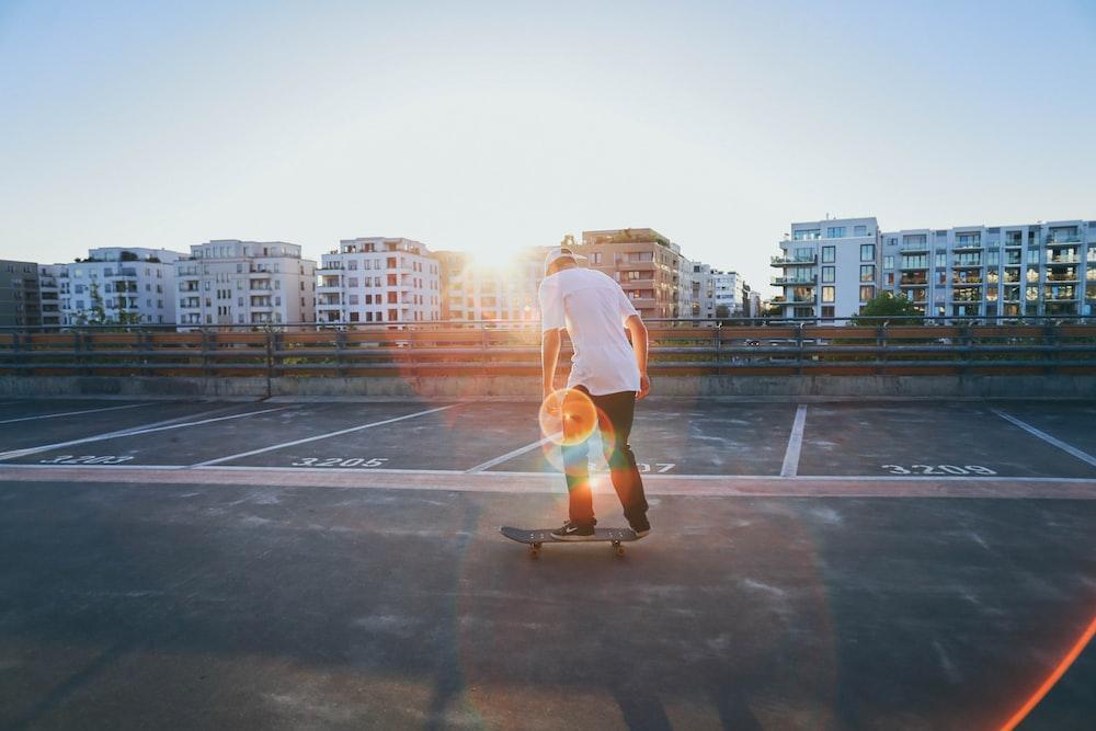man riding skateboard on parking lot near buildings during golden hour