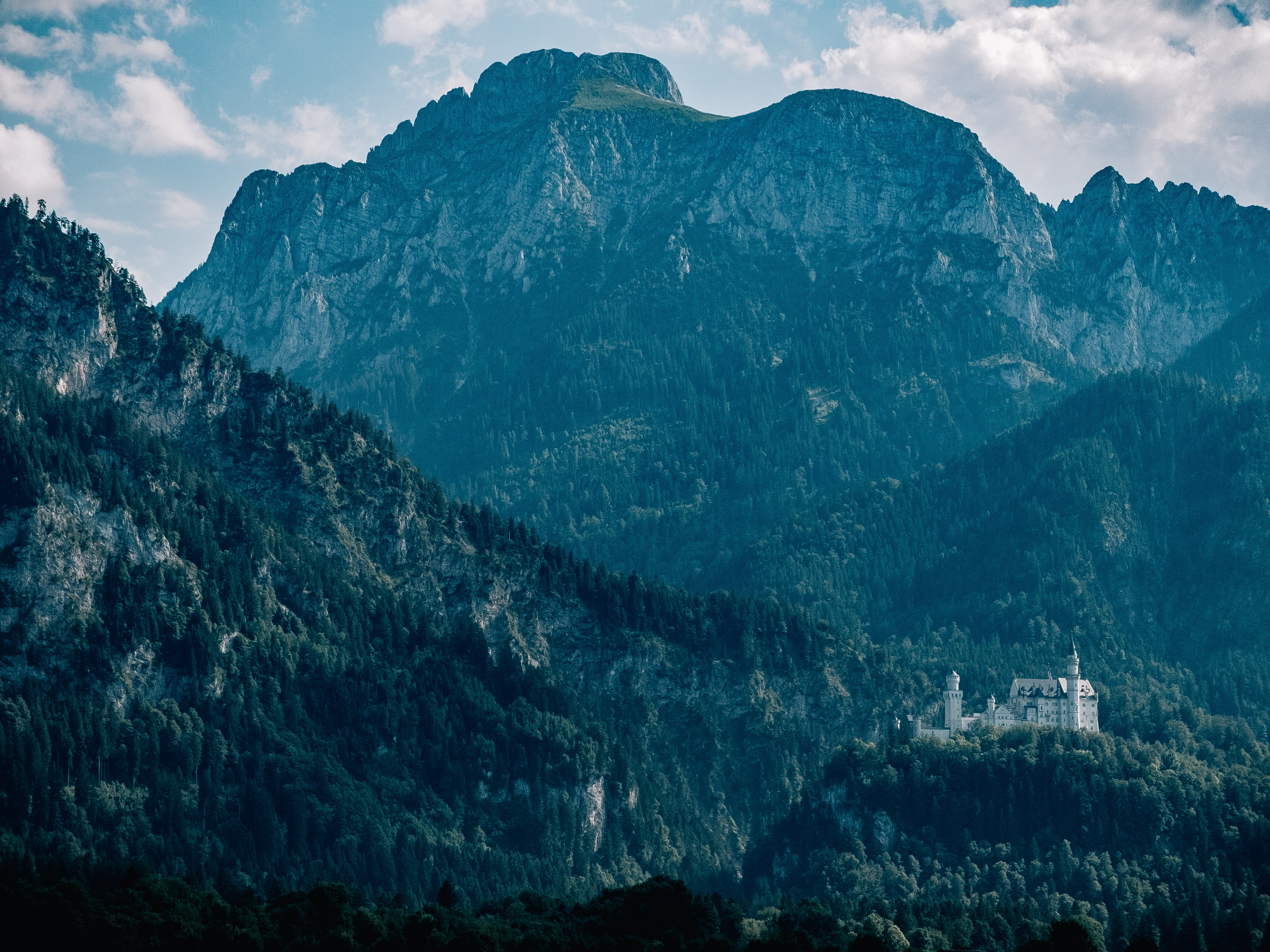 A scenic landscape with a rugged mountain ridge towering over the Neuschwanstein Castle