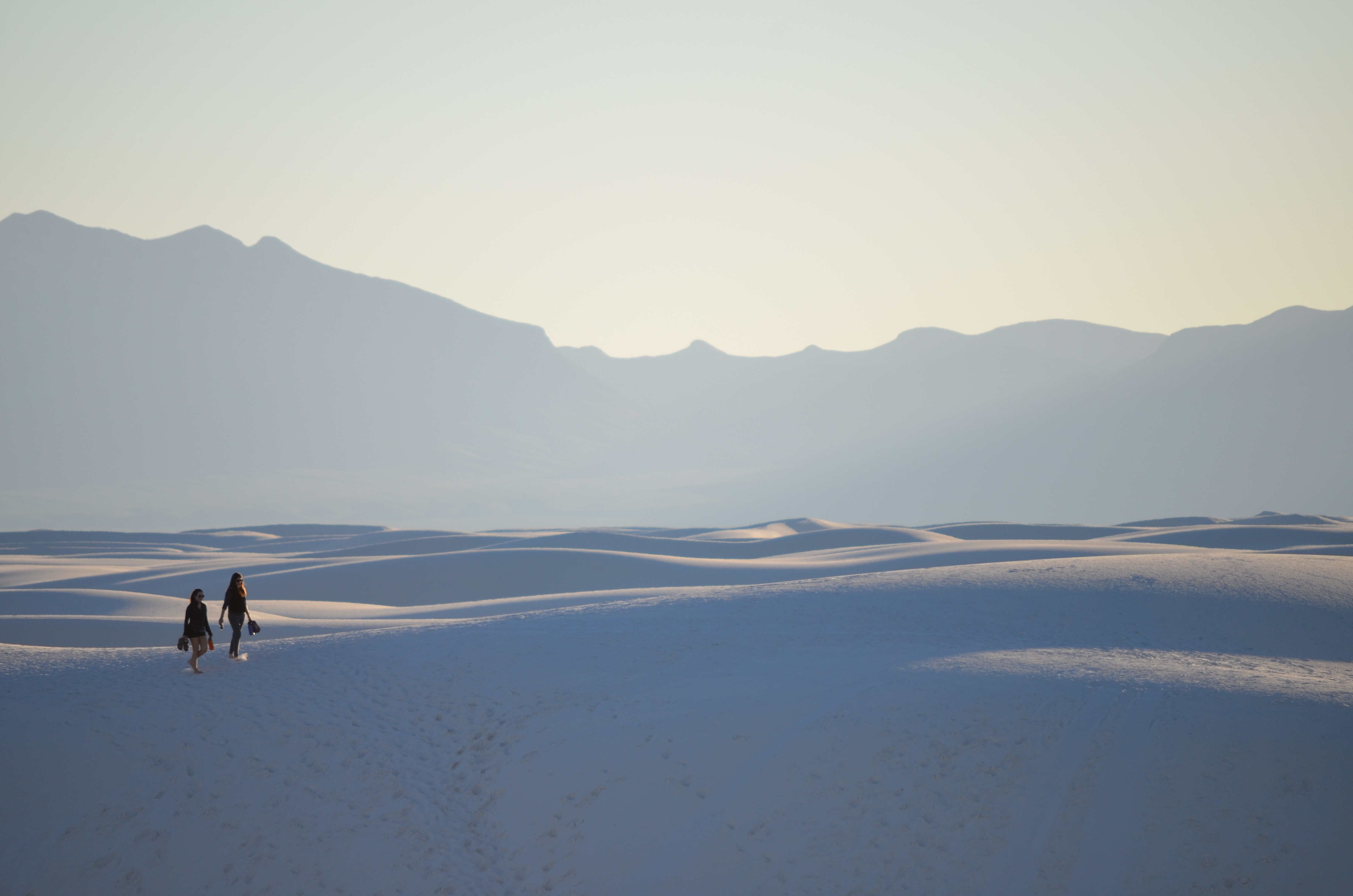 Two people hike through dunes in White Sands National Monument