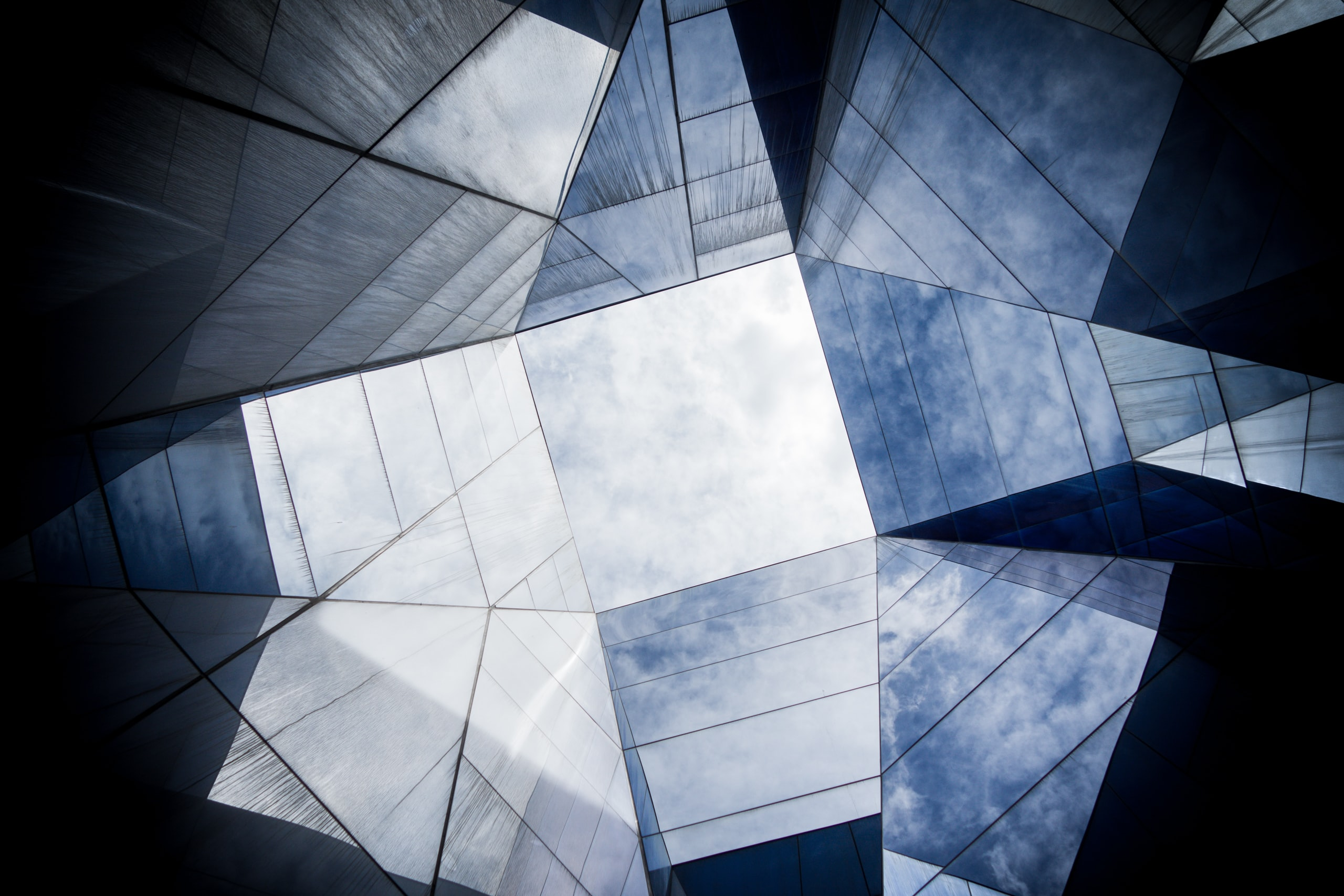 Cloudy sky seen through an abstract shape formed by the angled panes of a glass ceiling
