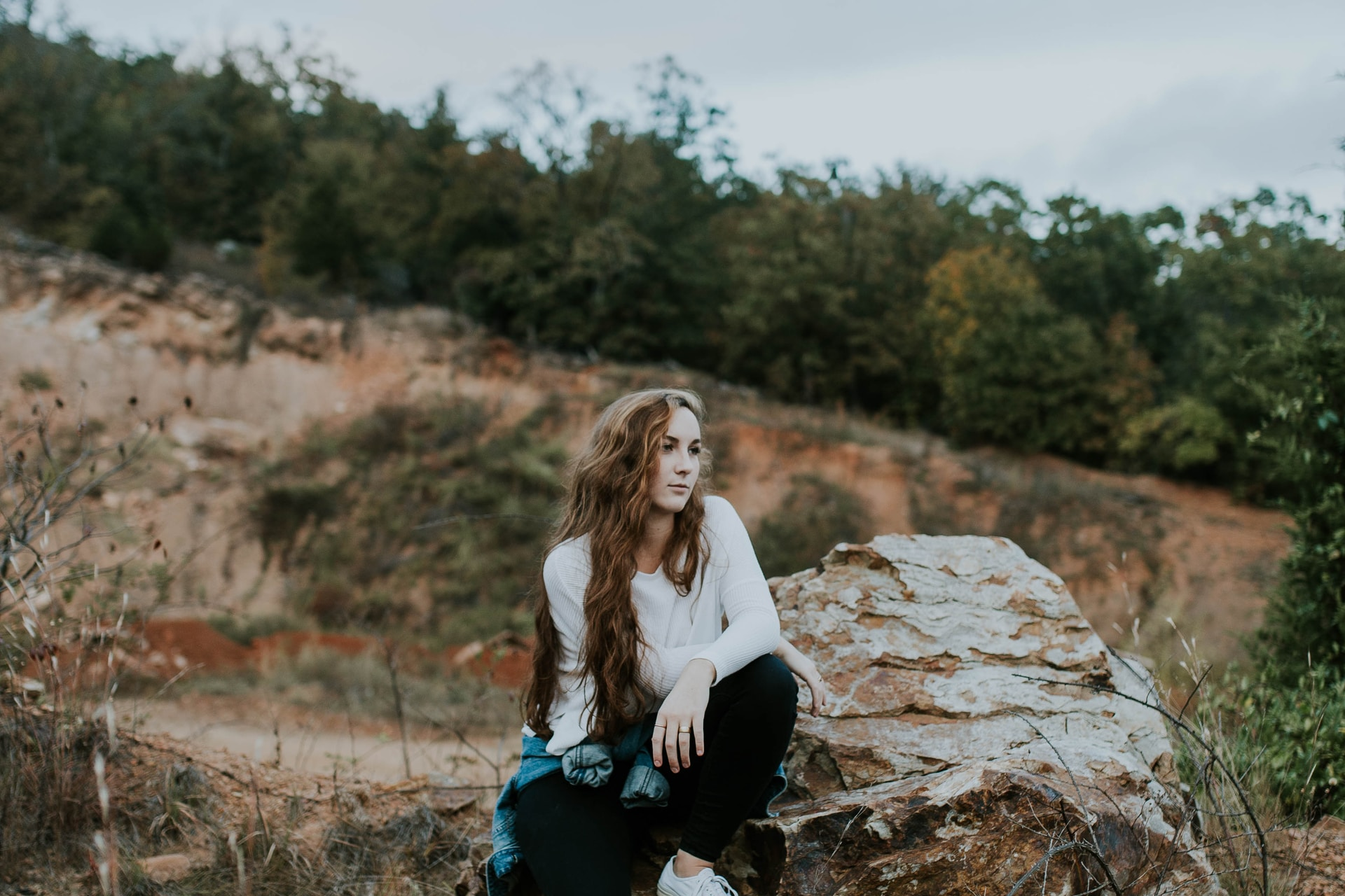 woman sitting on stone boulder outdoor