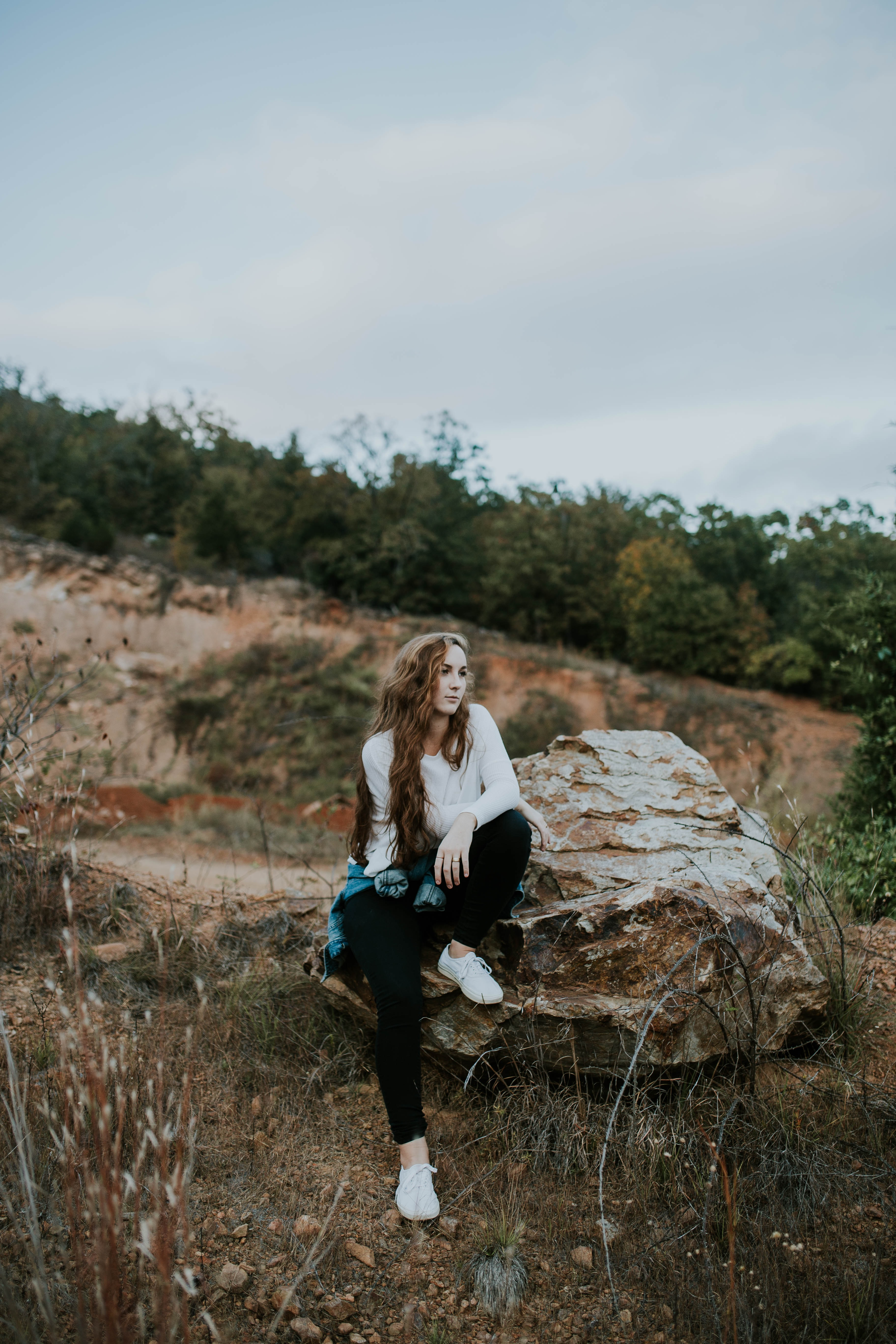 Young woman sitting on a large rock during a mountain hike