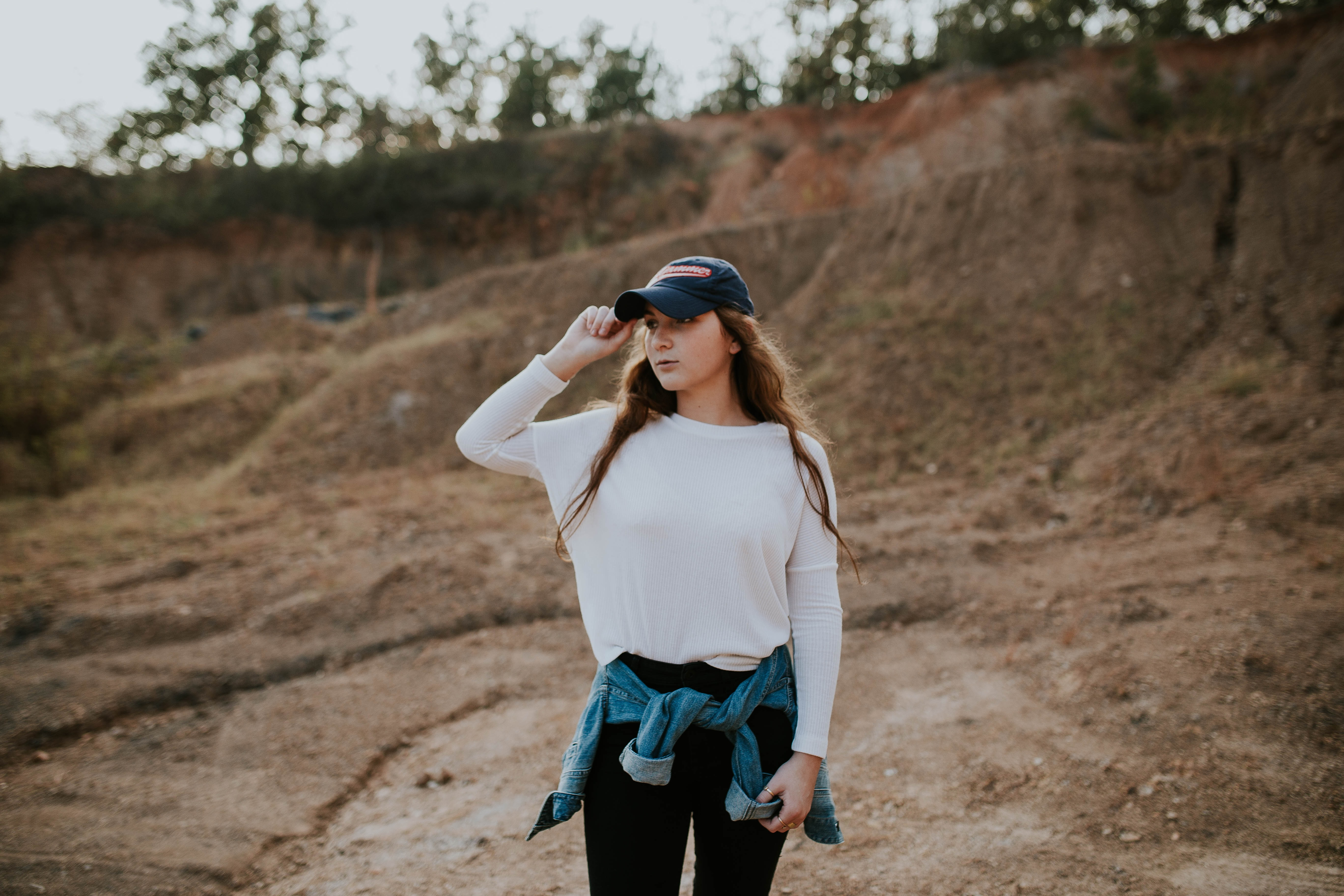 Woman in a baseball cap looking away while hiking alone
