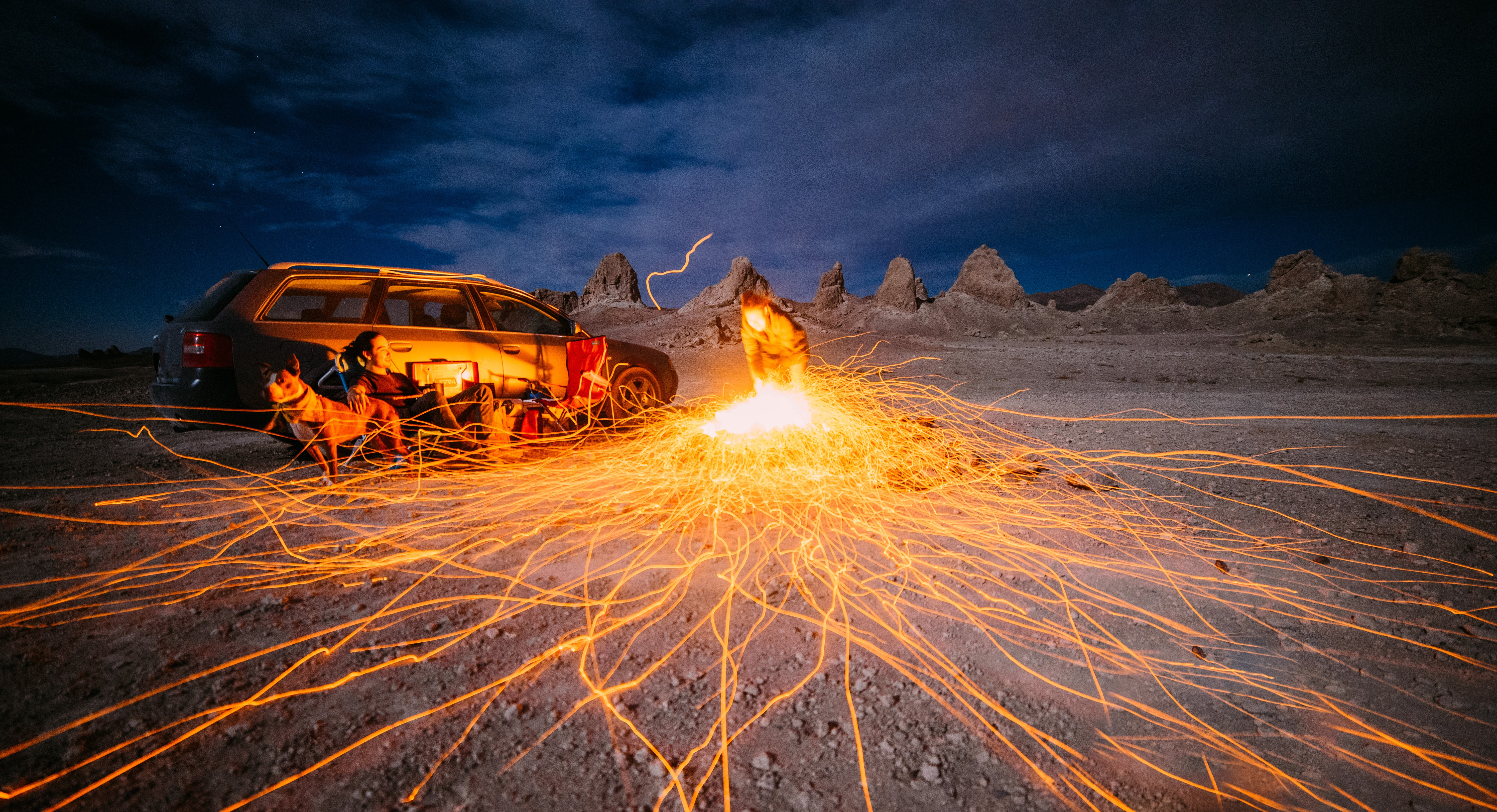 Campers next to a fire at night in the desert