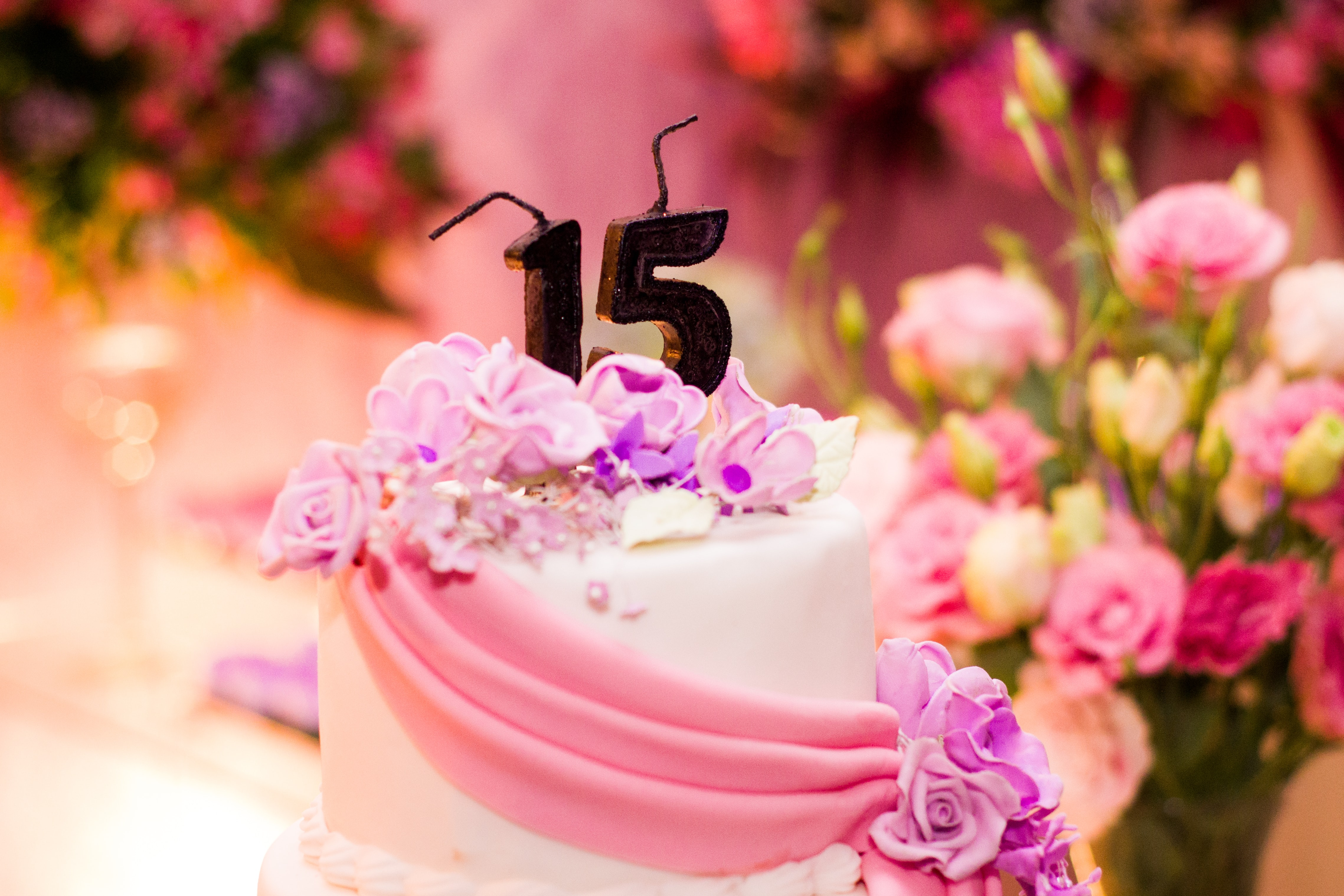 "A birthday cake decorated with flowers and candles in the shape of the number ""15"" at the top"