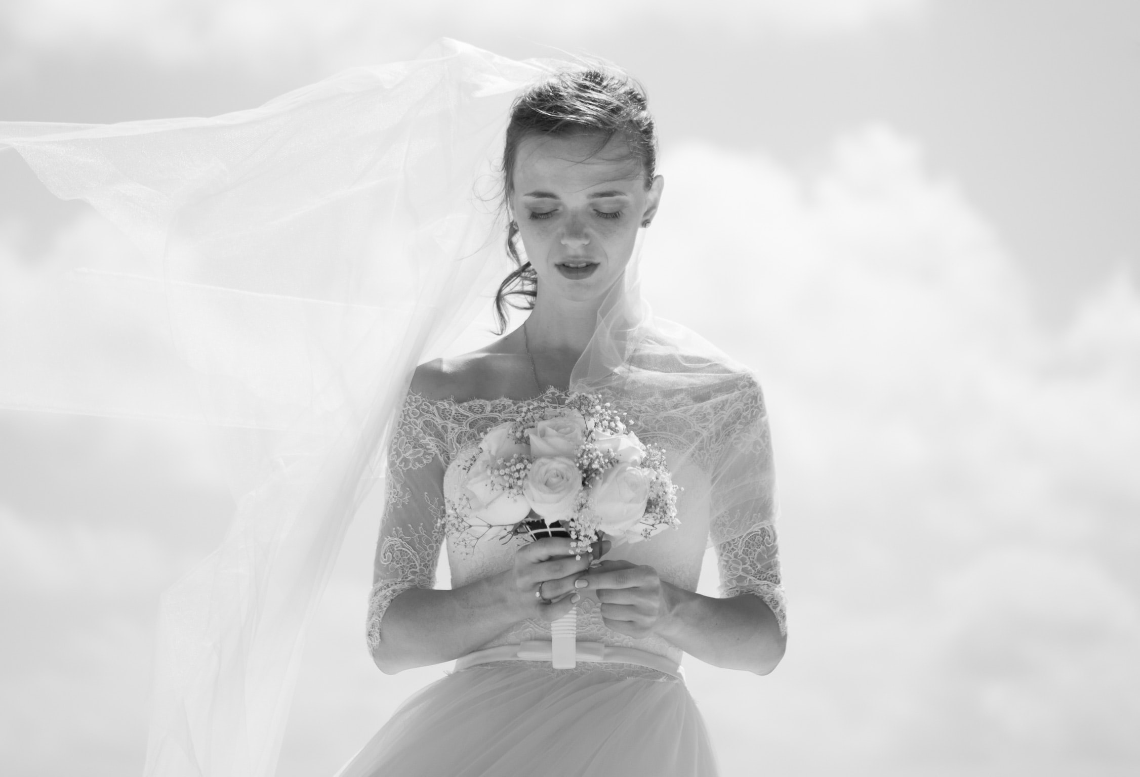 Black and white shot of beautiful bride with veil holding white flower bouquet with cloudy sky