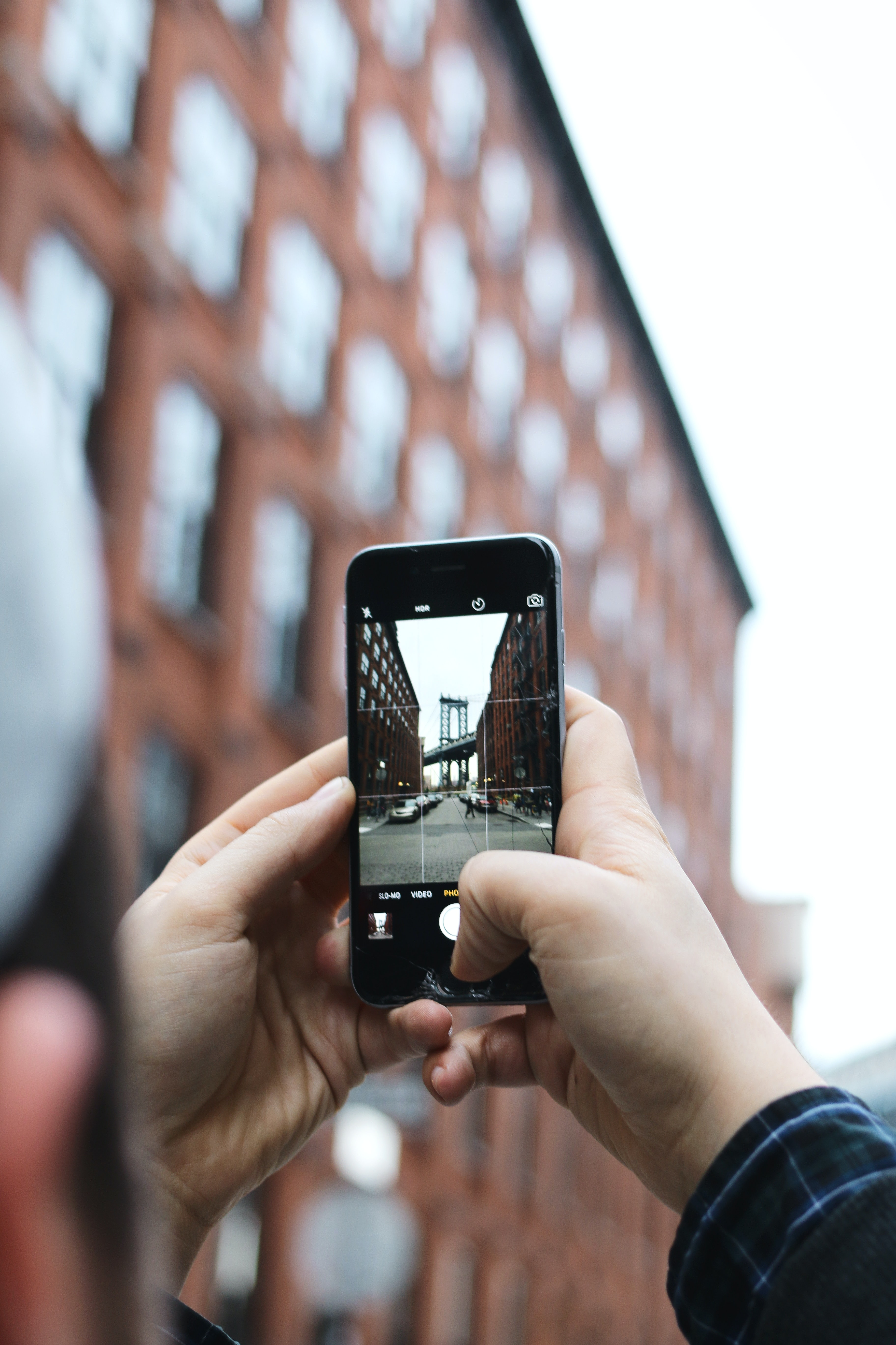 A person taking a picture of urban buildings with their phone.