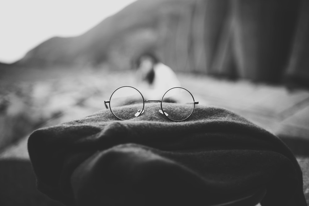 grayscale photo of hippie eyeglasses on cloth