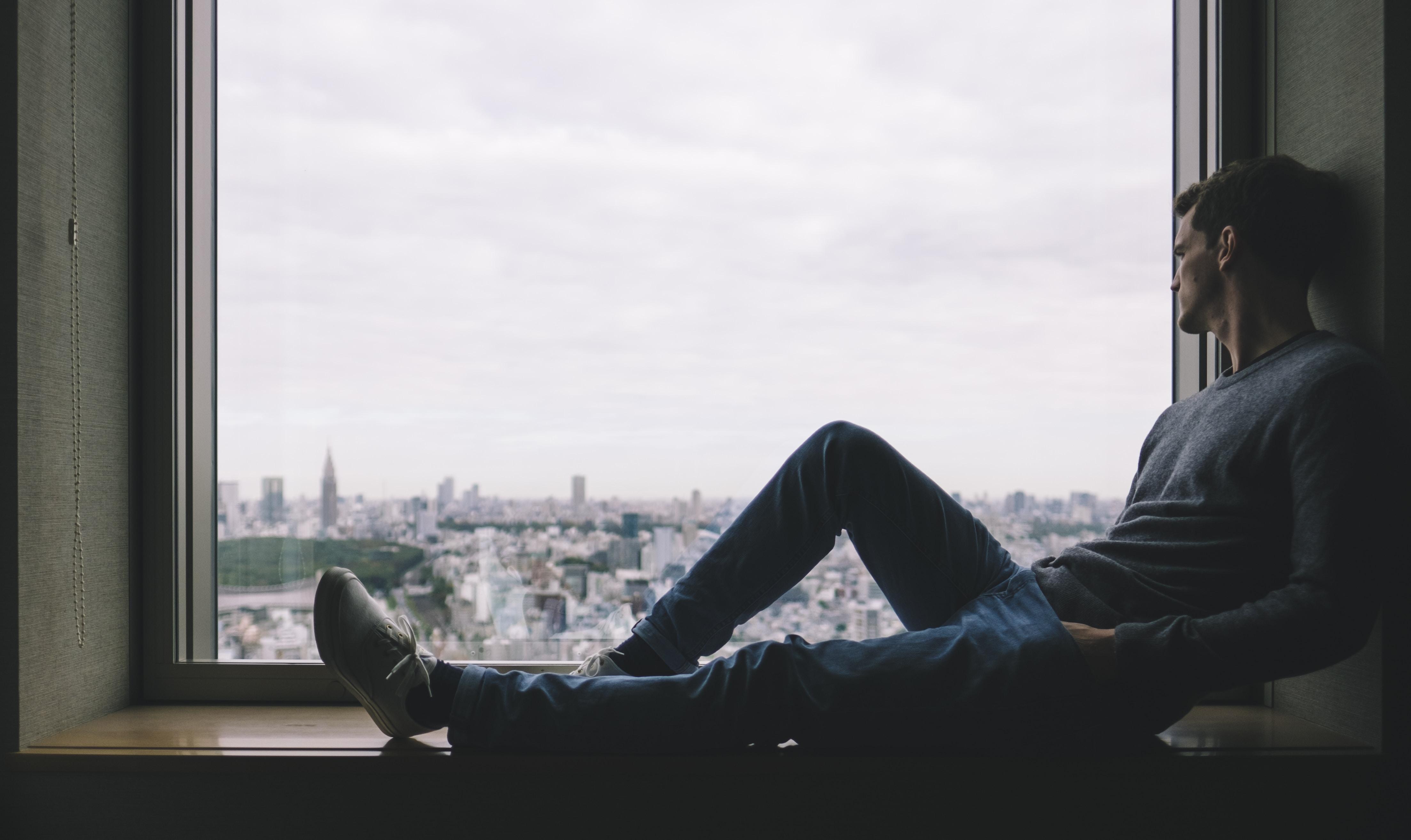 man sitting on brown wooden windowsill across buildings