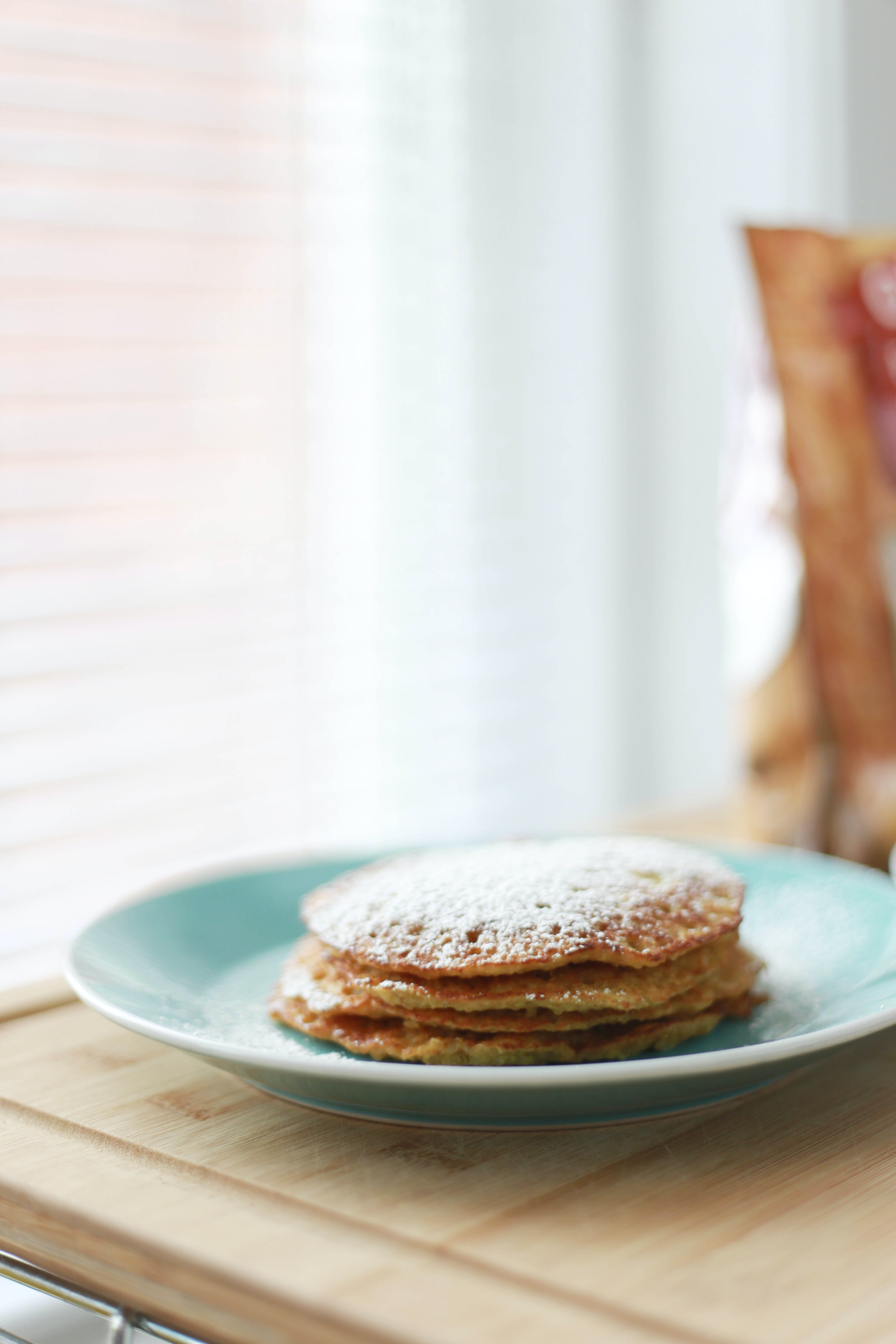 Pancakes covered with powdered sugar on a blue plate on a wooden table