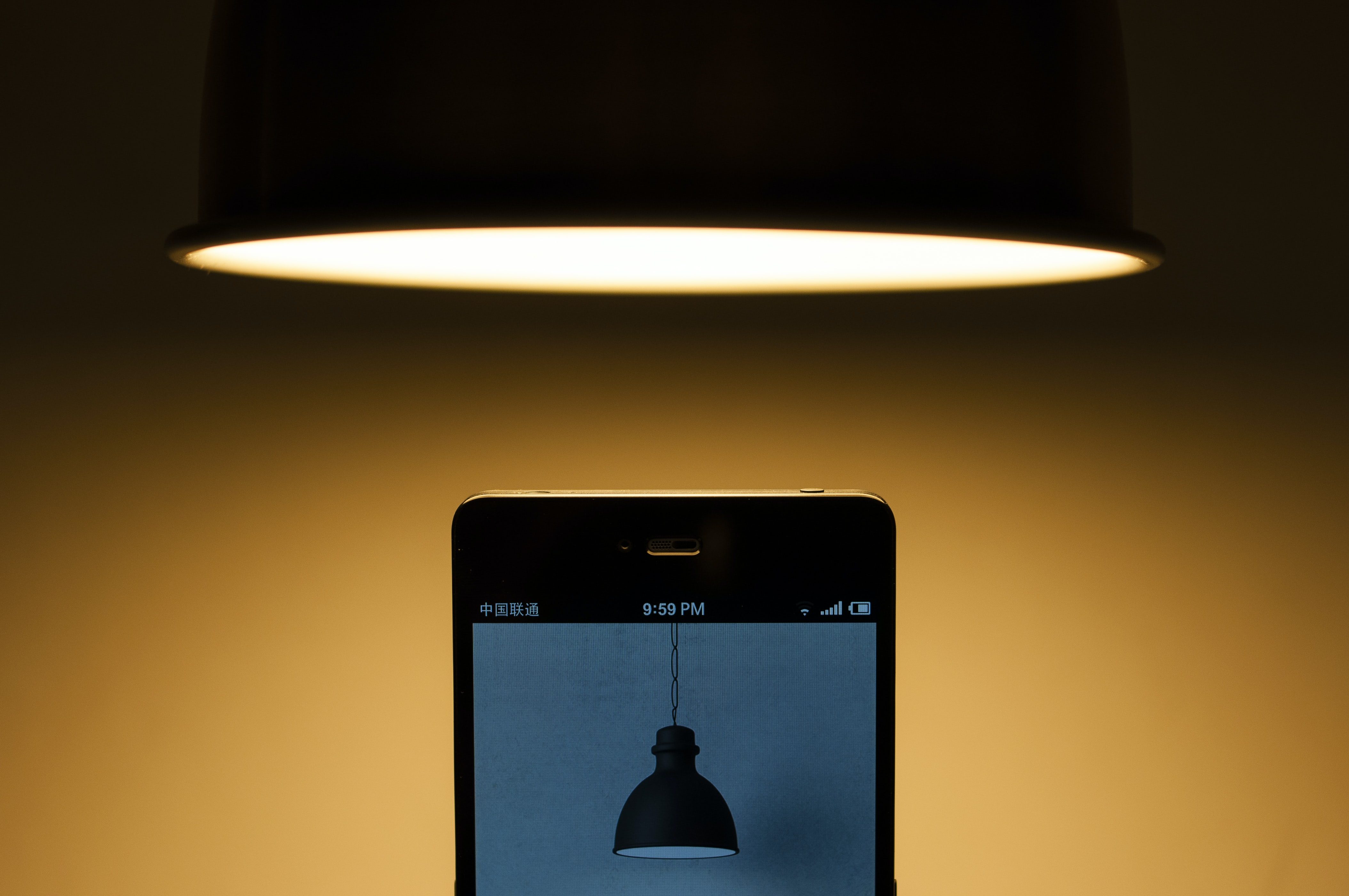 Lamp hangs above cellphone that displays a photo of a lamp