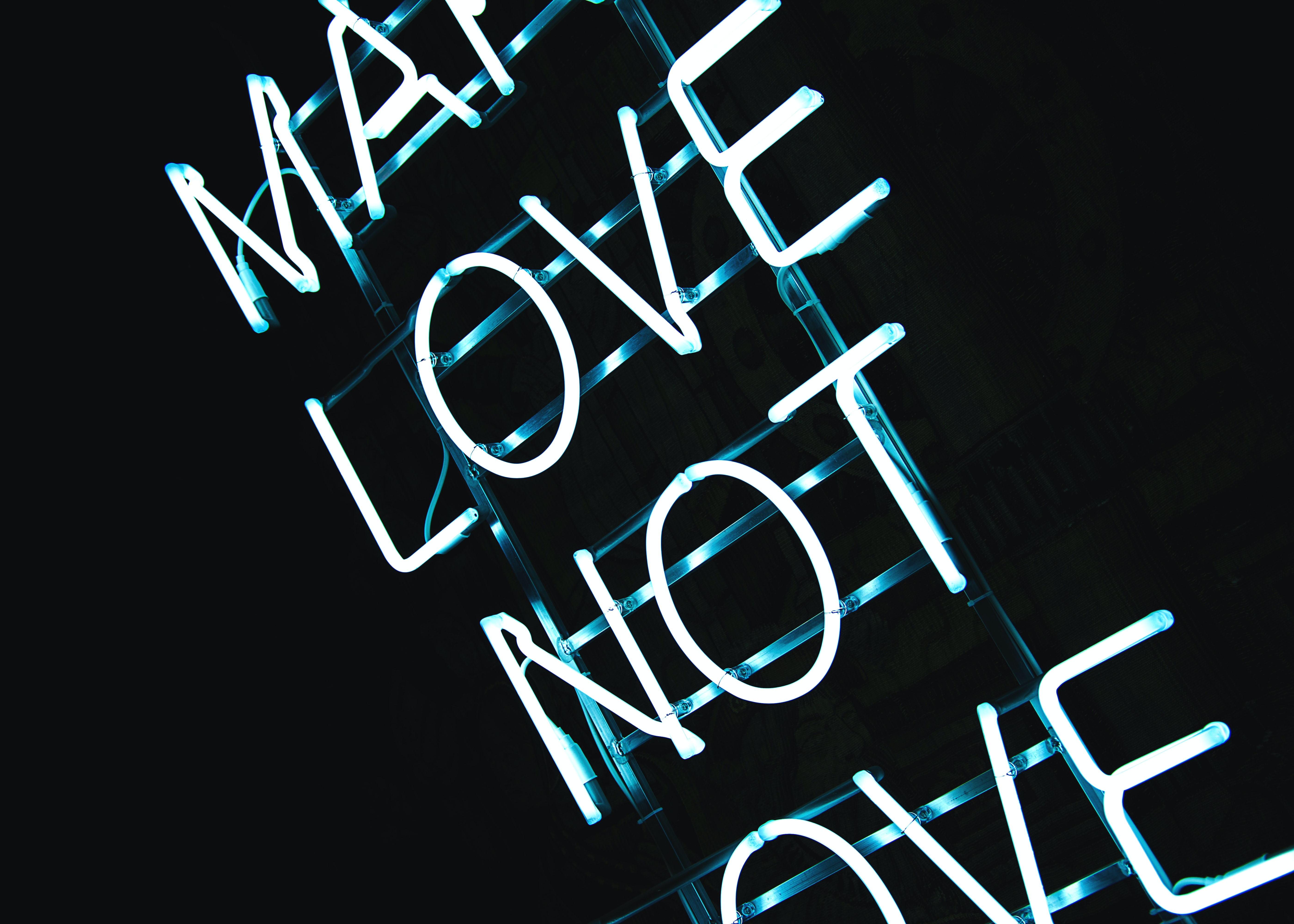 Blue neon light sign on black background reads Make Love Not Love