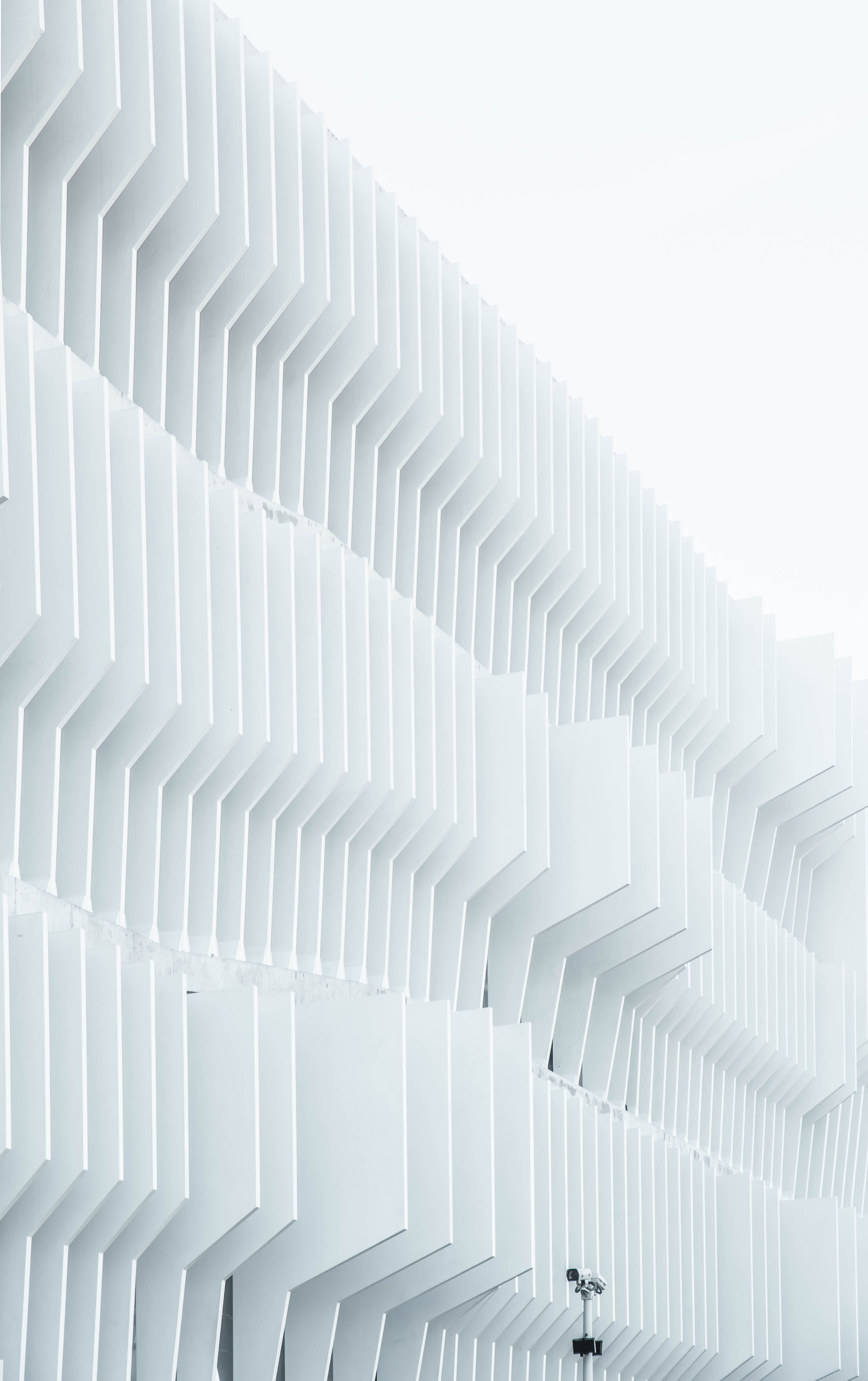 A security camera near parallel white ribs in a building facade in Madrid