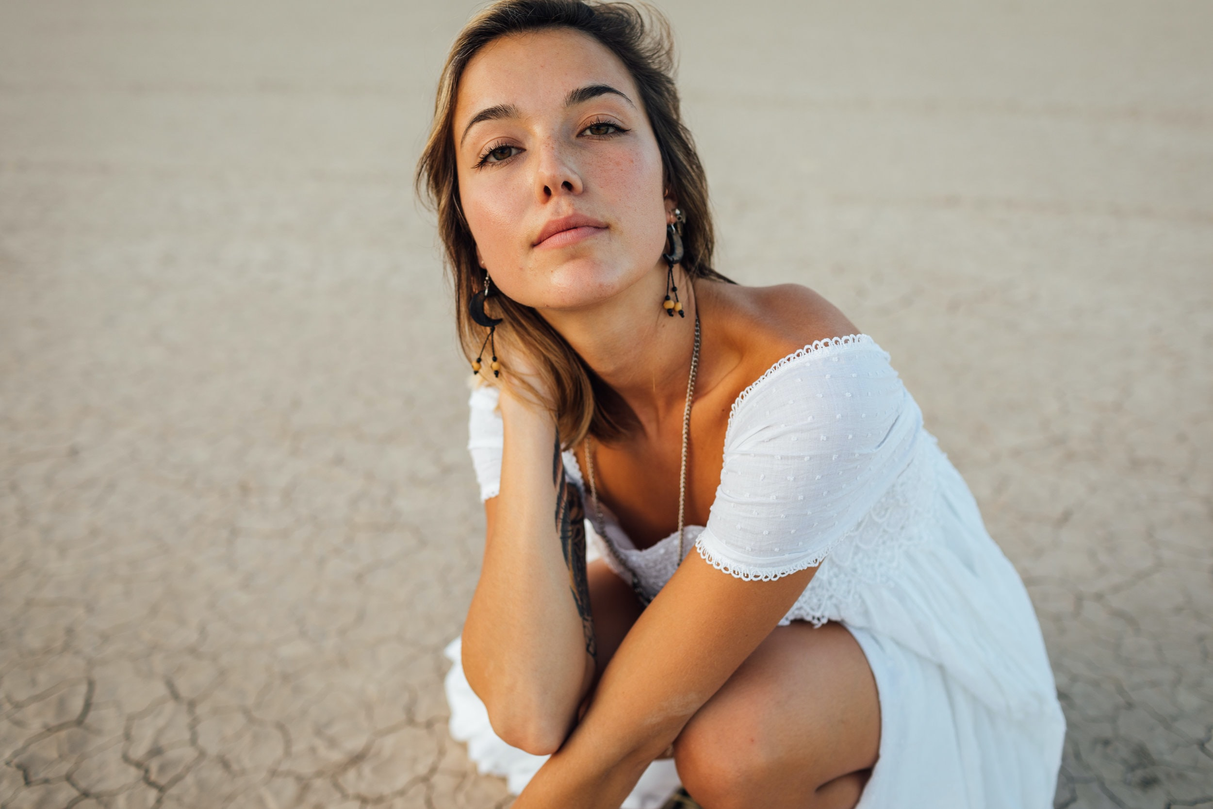 woman wearing white off-shoulder dress sitting on sand