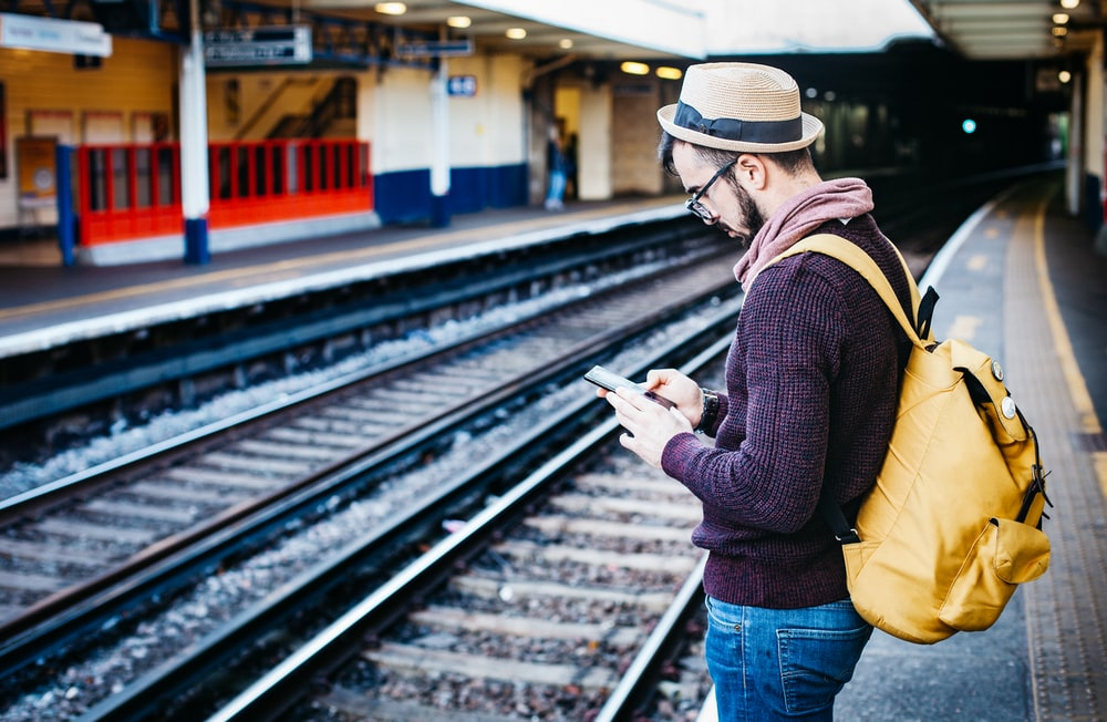 man using phone while standing in front of train rail during daytime