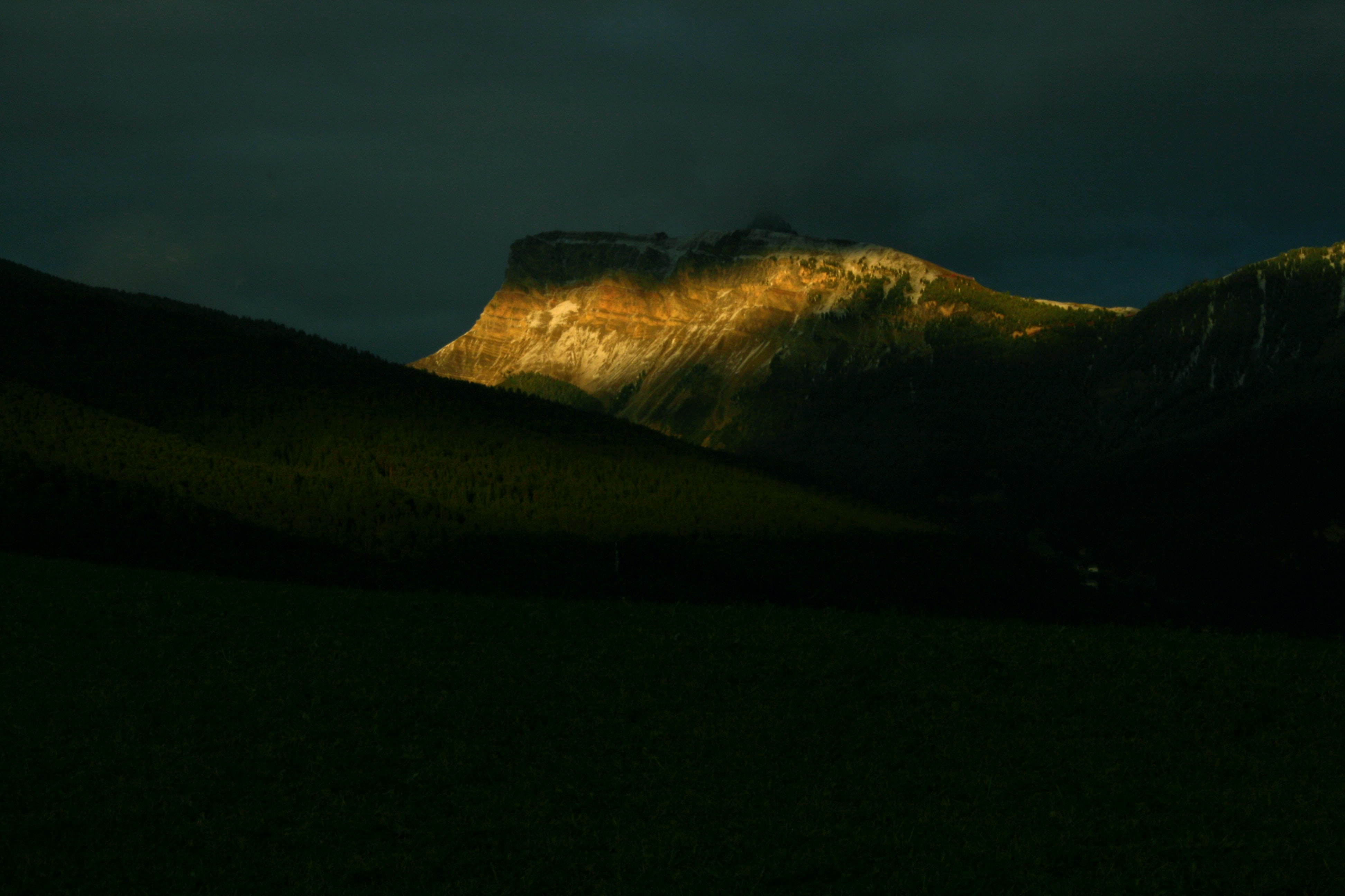The last rays of sunshine fall on a tall mountain as the evening sets in