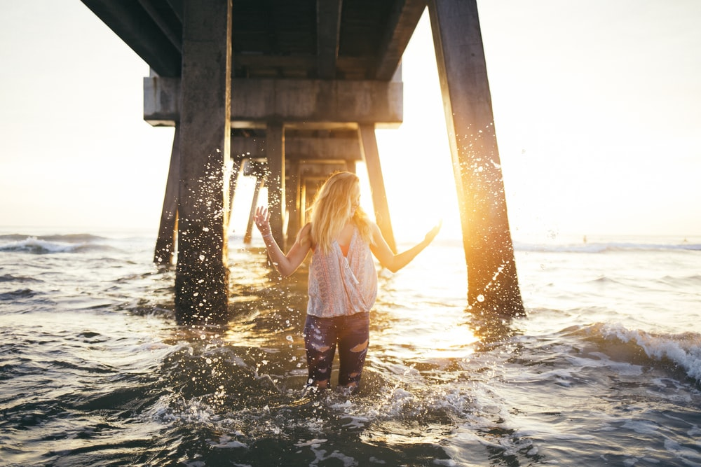 woman stading in water under a dock during golden time