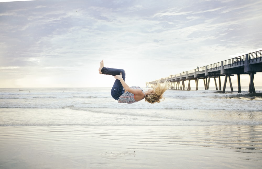 woman doing a back flip on beachshore