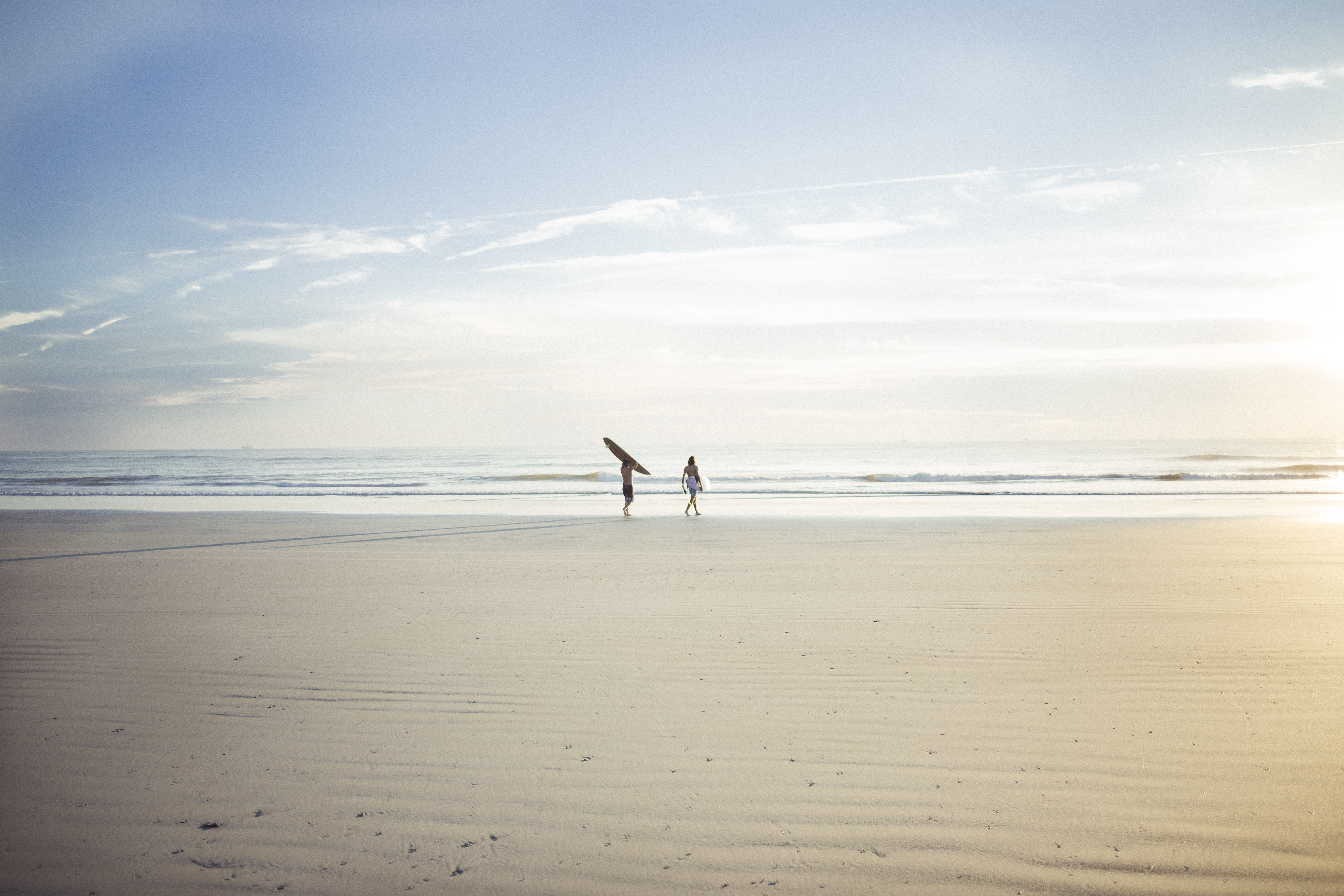 Two surfers walking on the sandy beach towards the ocean