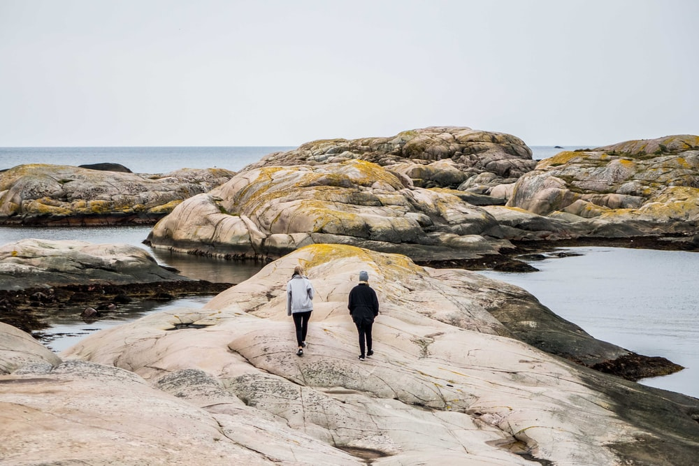 woman and man walking on rock formation near body of water during daytime