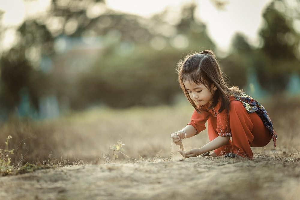 a little girl wearing orange red playing in the sand in cao lnh - Kids Pic Download