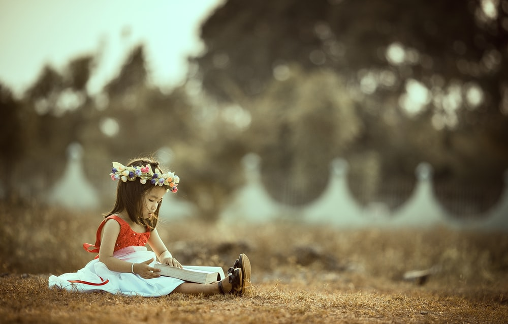 A little girl wearing a party dress and flower crown, sitting in a field in Cao Lãnh, reading a book