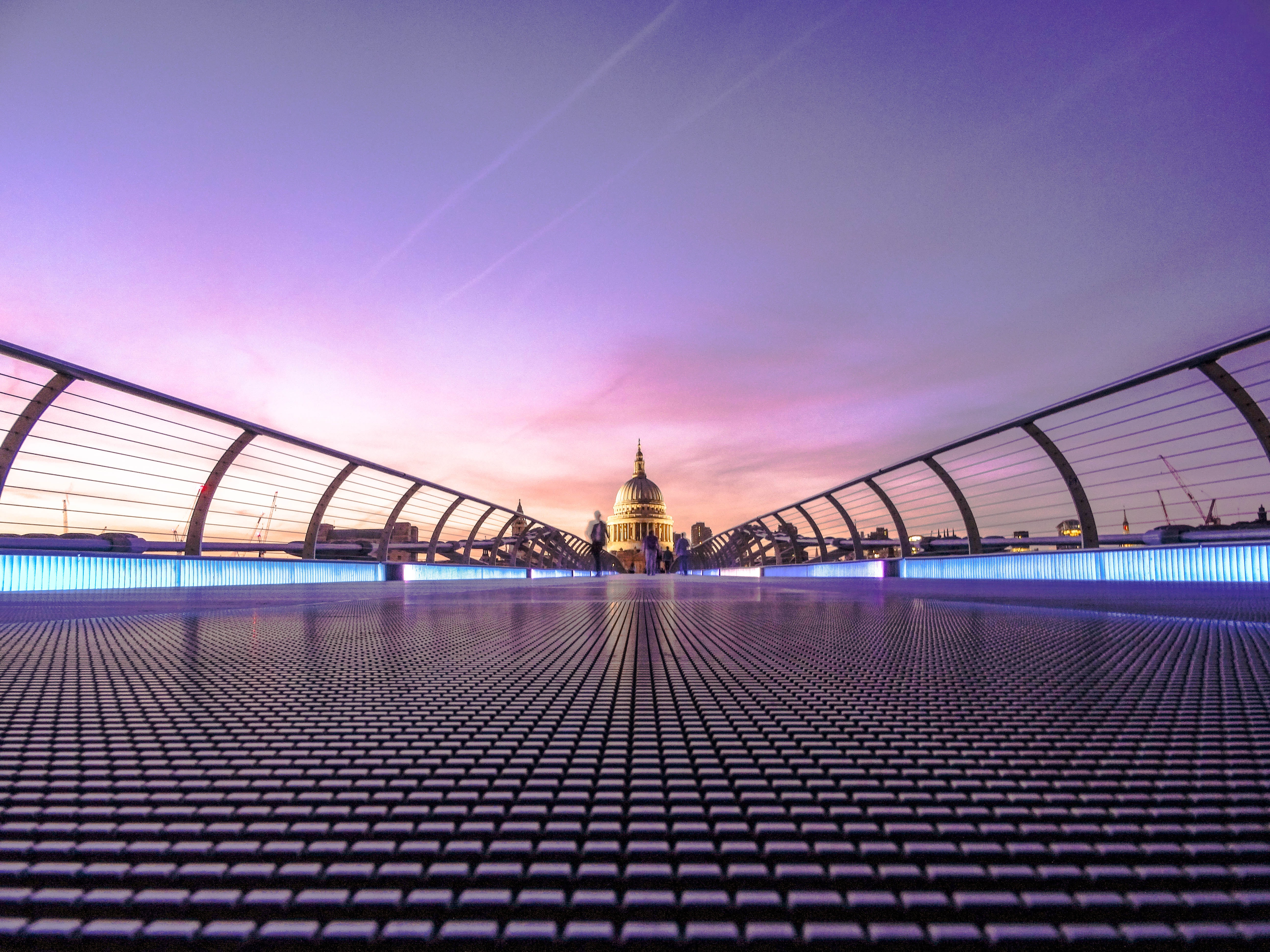 A low shot of people on the Millennium Bridge in London with a view on St. Paul's Cathedral